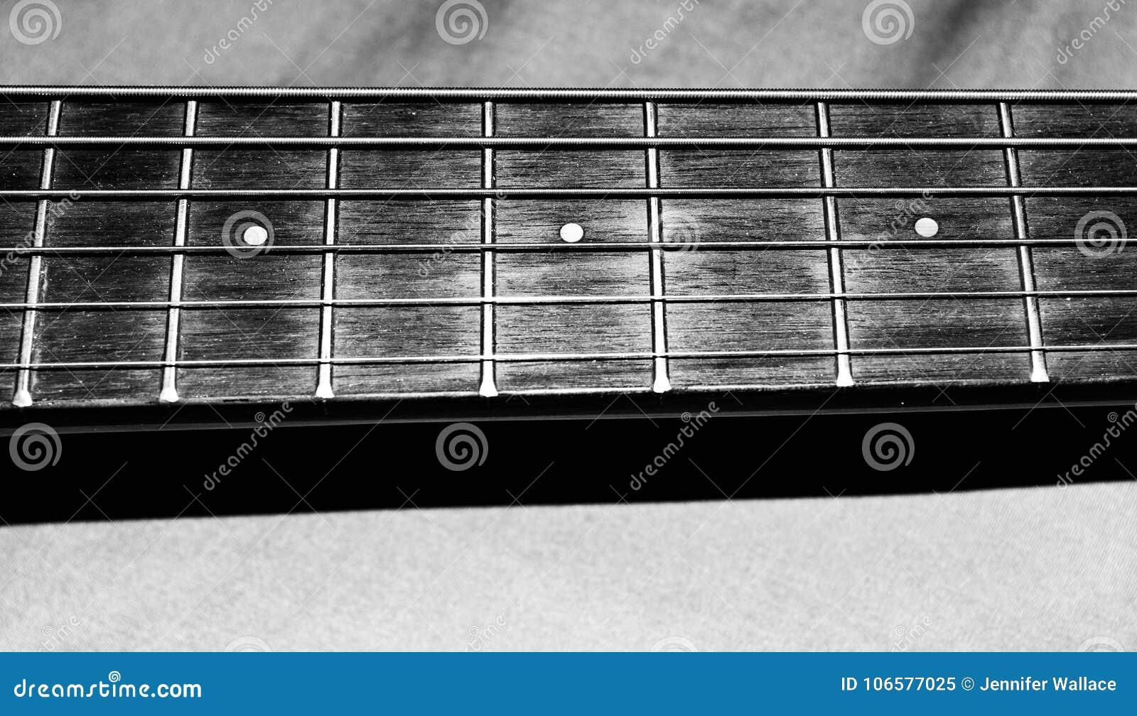 Foto preto e branco de cordas de uma guitarra acústica do ` s da criança e de fricções imediatamente após a guitarra para lições