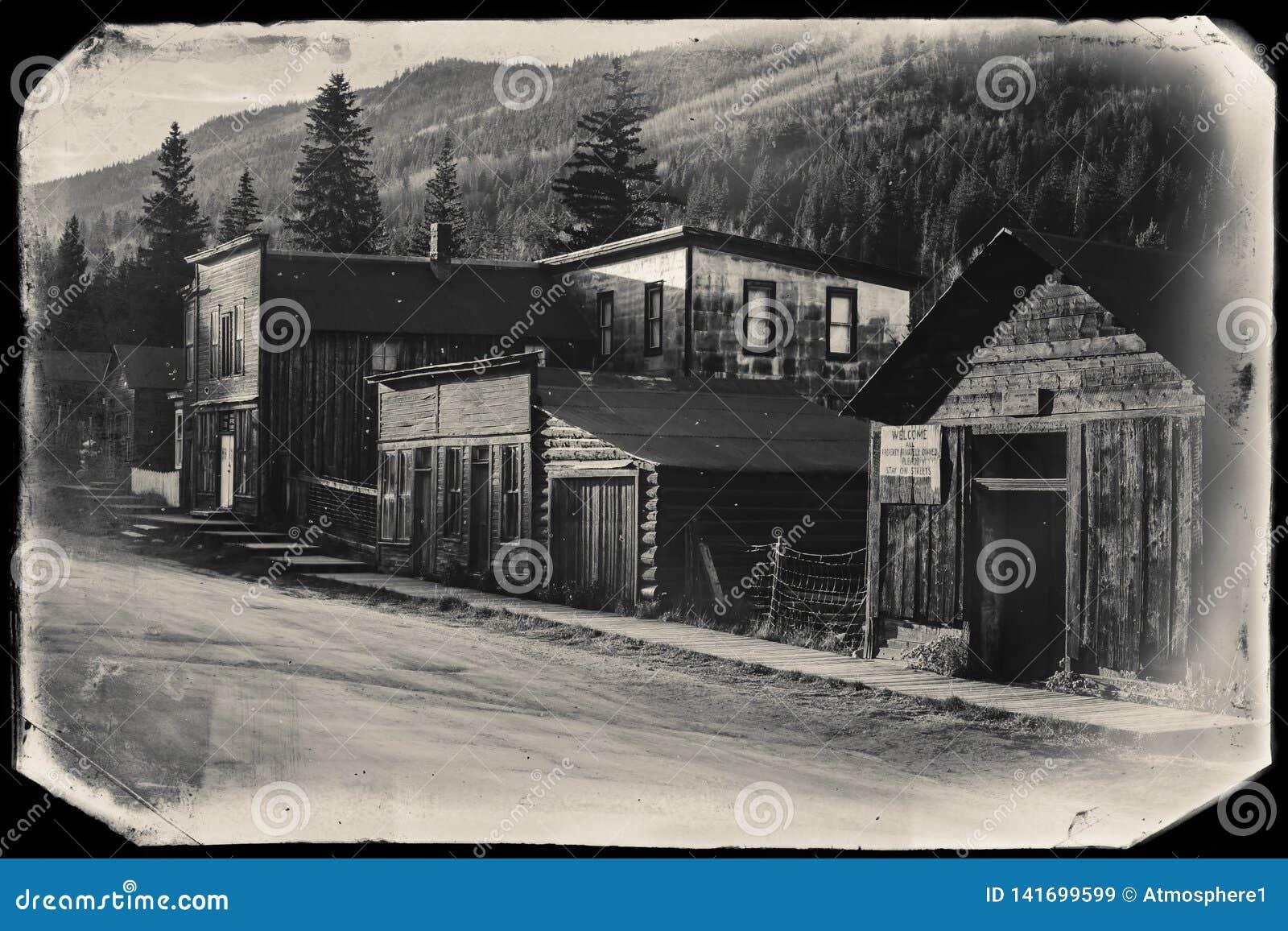 Foto preto e branco do vintage do Sepia de construções de madeira ocidentais velhas em St Elmo Gold Mine Ghost Town em Colorado
