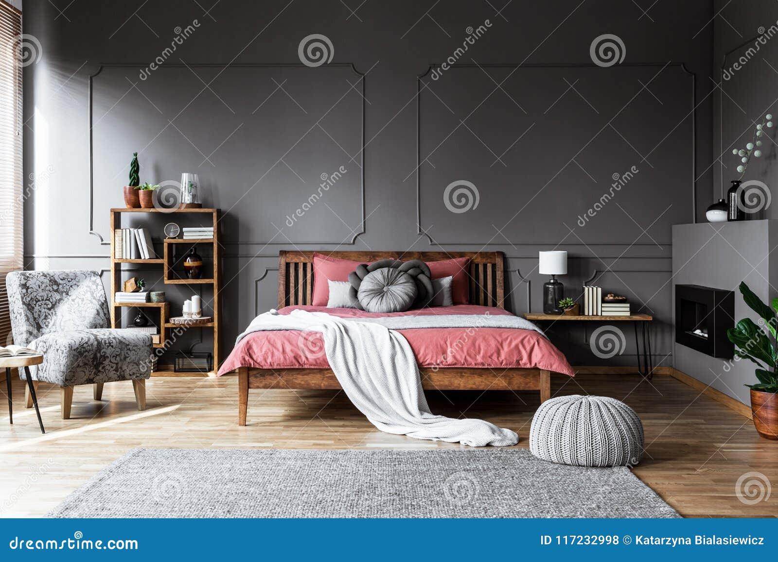 Foto real de um interior acolhedor do quarto com a cama de madeira no meados de