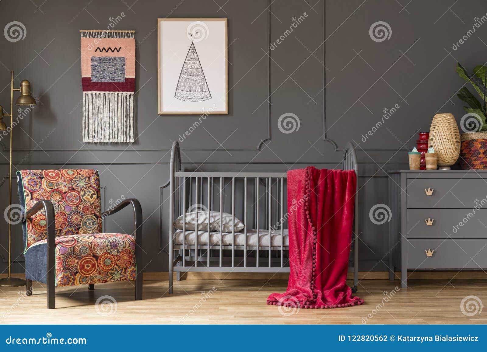 Foto real de un pesebre del bebé con una manta roja, una butaca, lámpara