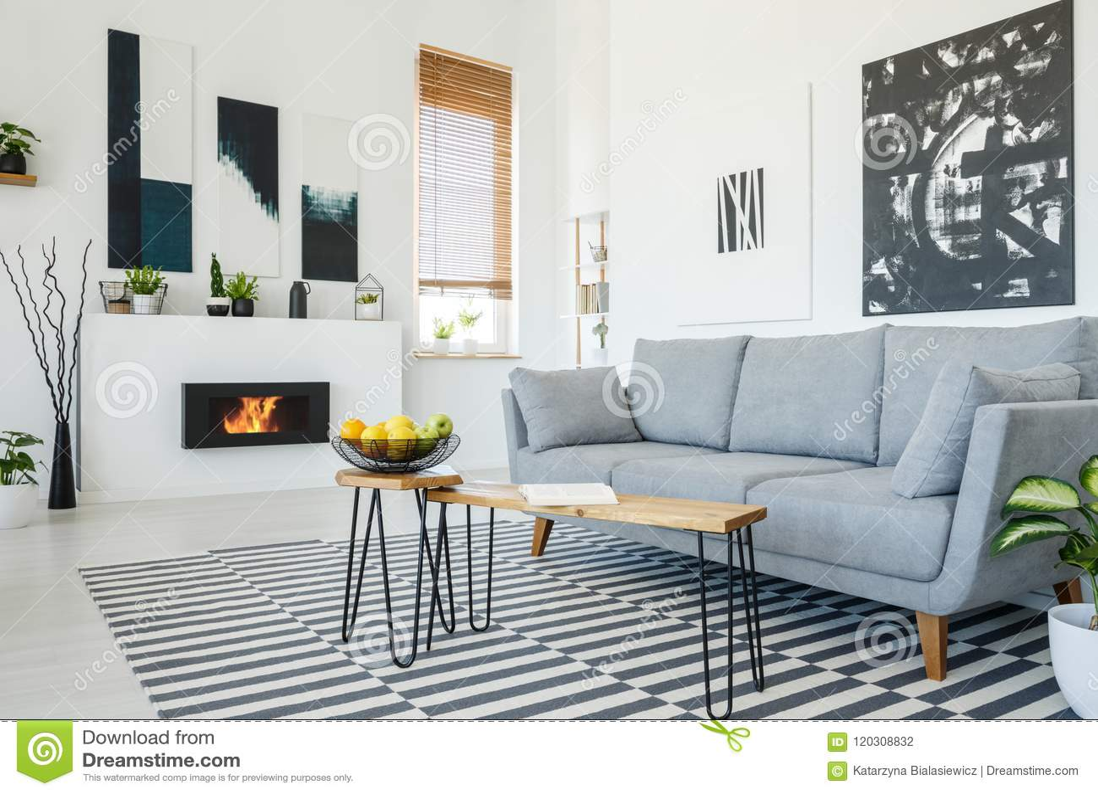 Foto real de un sofá gris que se coloca delante de una tabla de madera adentro