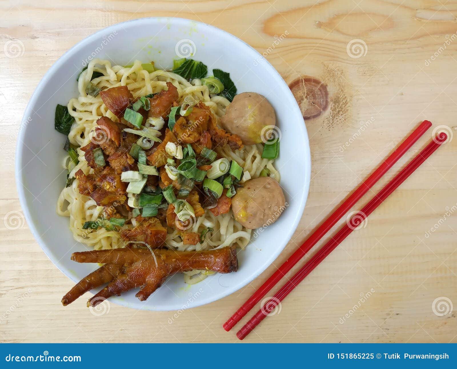 Foto simples, configuração lisa, bakso delicioso do ceker de Mie Ayam, macarronete da galinha na bacia branca e hashi plástico ve