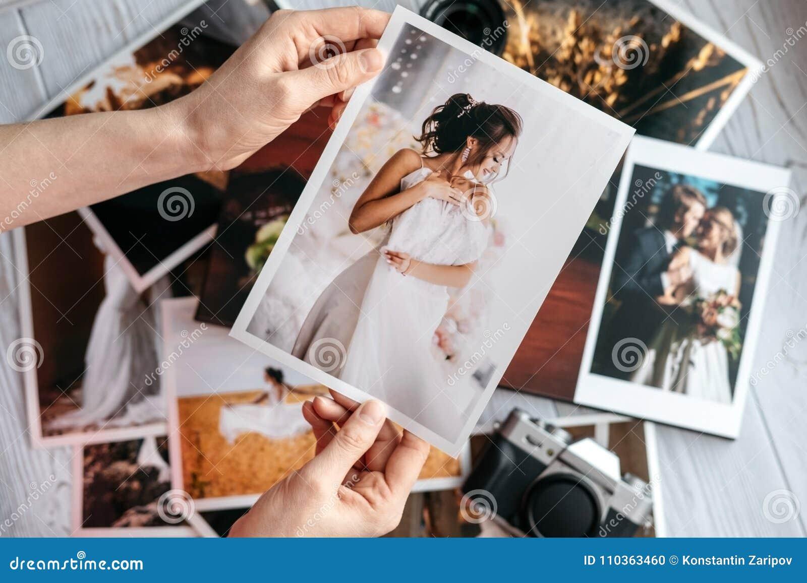 Foto stampate di nozze con la sposa e lo sposo, una macchina fotografica nera d annata e mani della donna con la foto