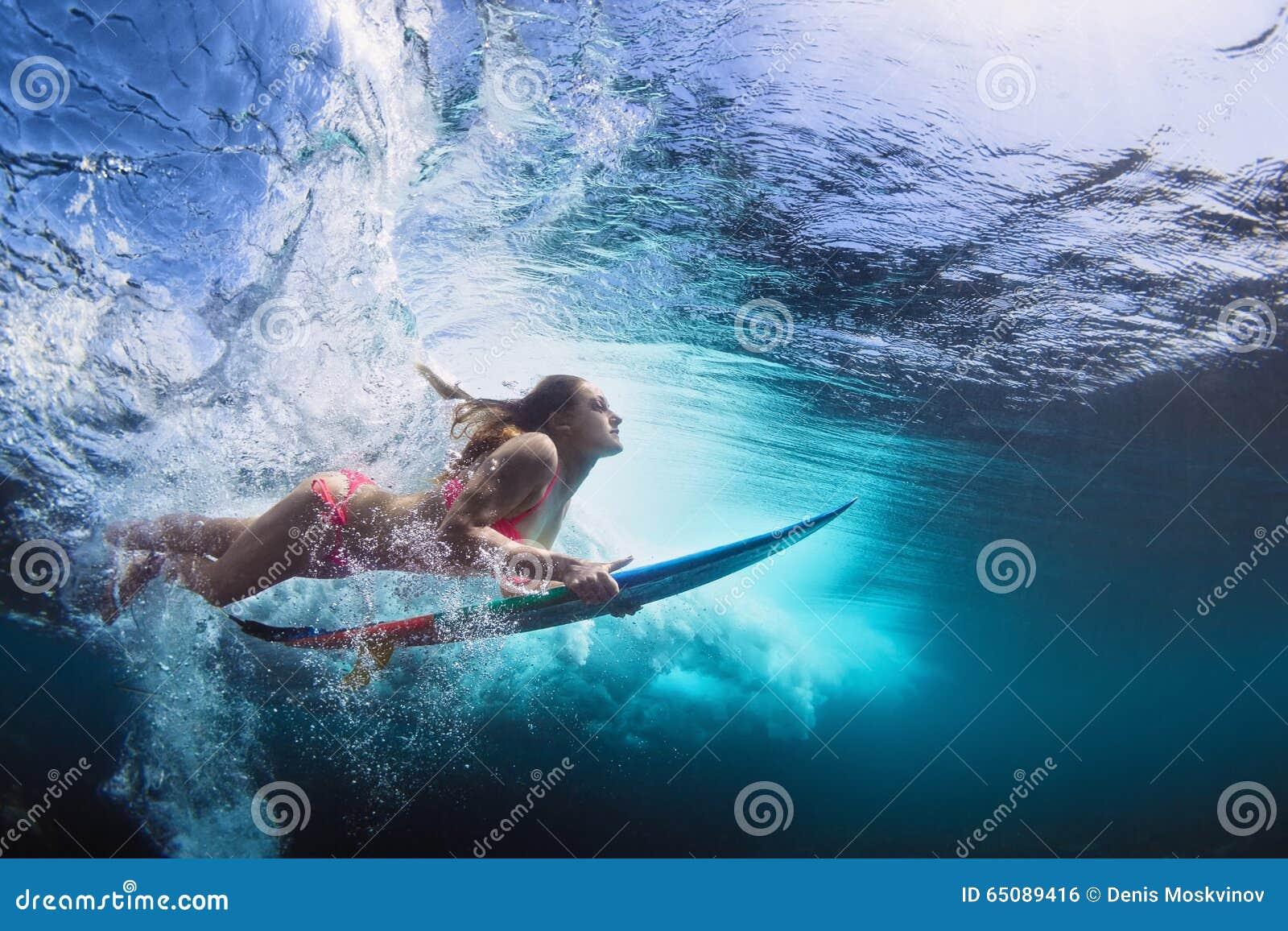 Foto subaquática da menina com mergulho da placa sob a onda de oceano