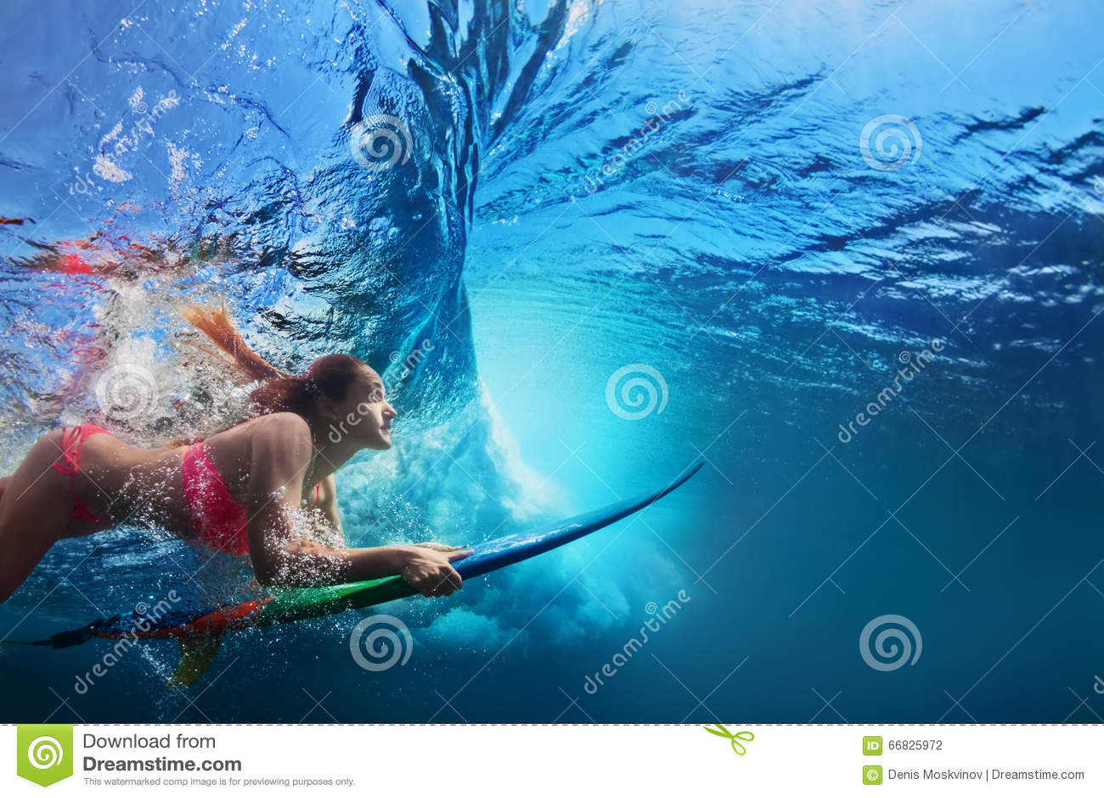 Foto subaquática do mergulho da menina do surfista sob a onda de oceano