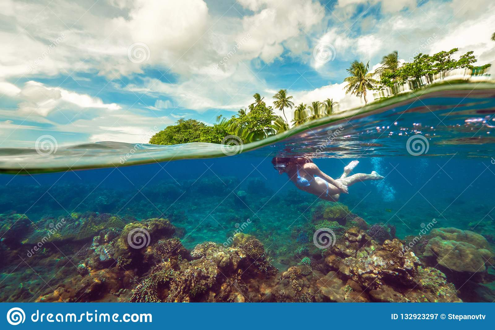 Foto subaquática rachada de uma menina que mergulha com máscara no oceano tropical que aprecia férias de verão na ilha exótica