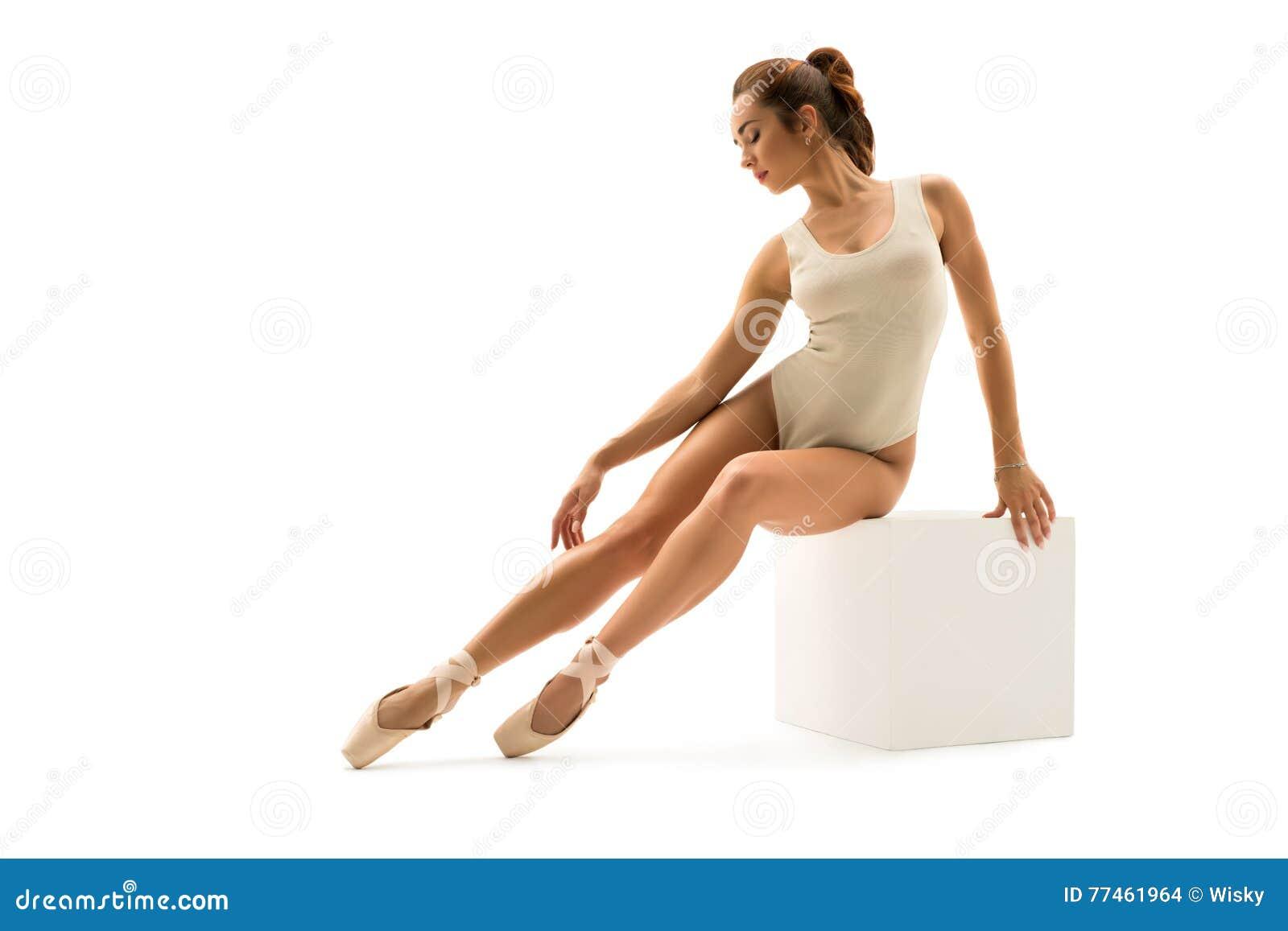 Foto van balletdanser die elegant op kubus zitten