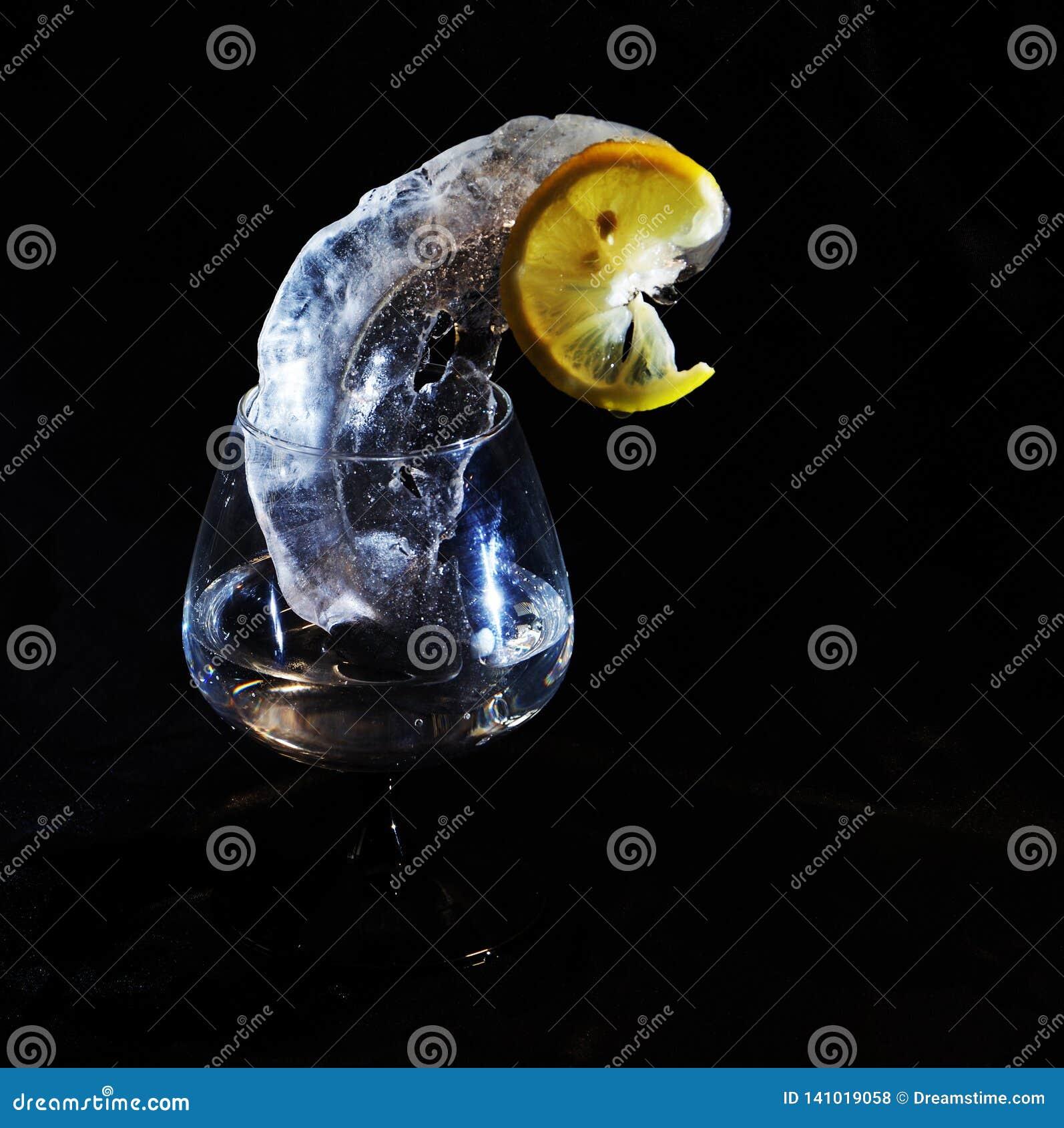 Foto van citroen en ijs in gele en zwarte kleuren in wijnglas