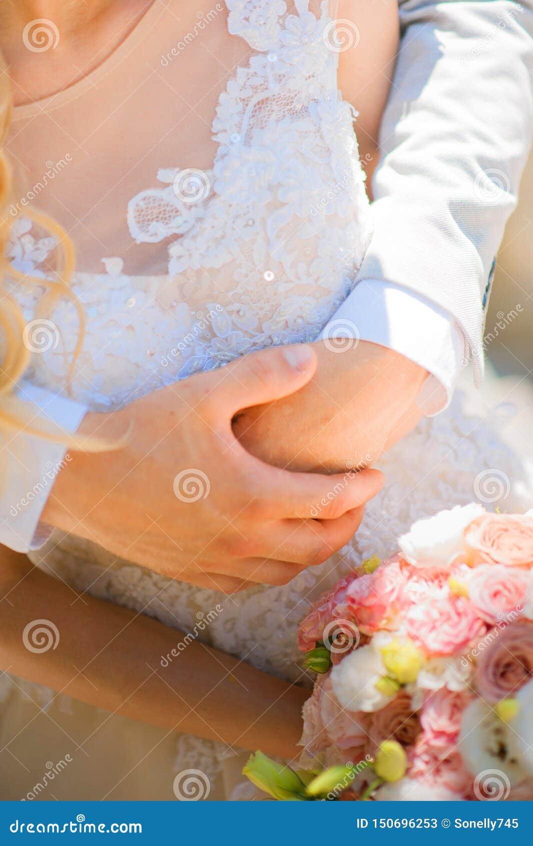 Foto van een huwelijkspaar in de zomer Bruid en bruidegom het koesteren, handen, ringen, het close-up van het huwelijksboeket en