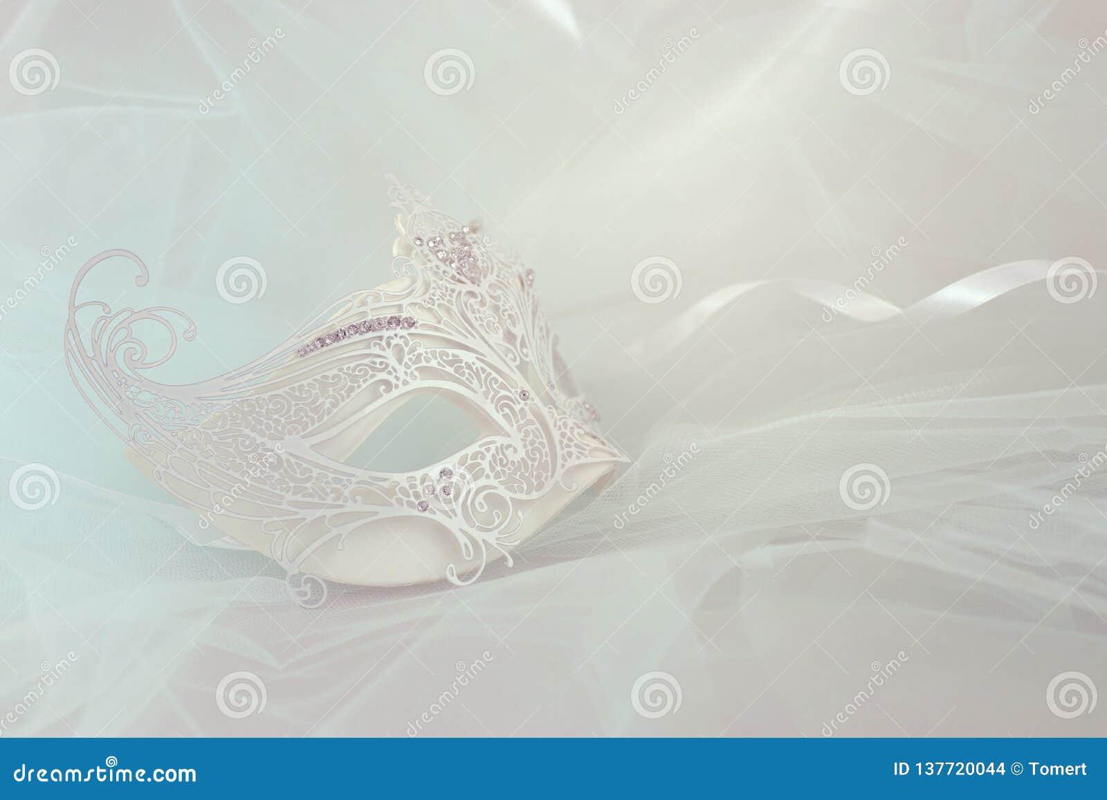 Foto van elegant en gevoelig wit kant Venetiaans masker over de achtergrond van de muntchiffon