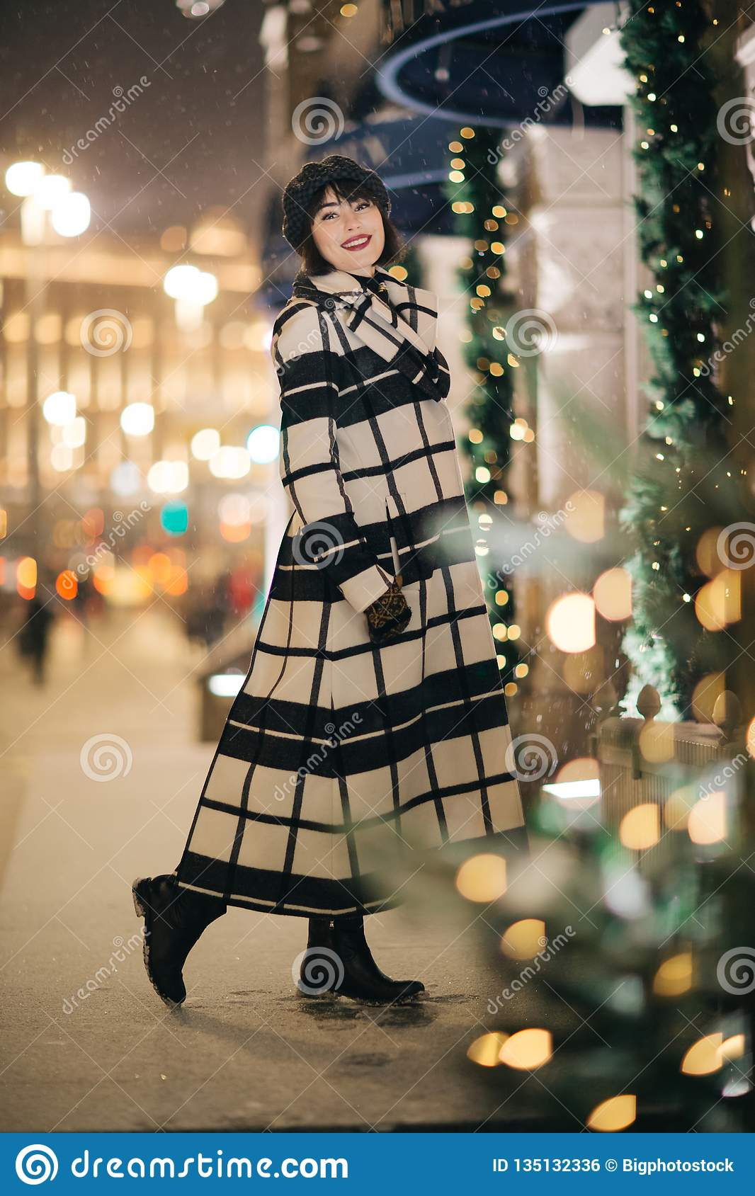 Foto van het brunette van gemiddelde lengte in straat op vage achtergrond