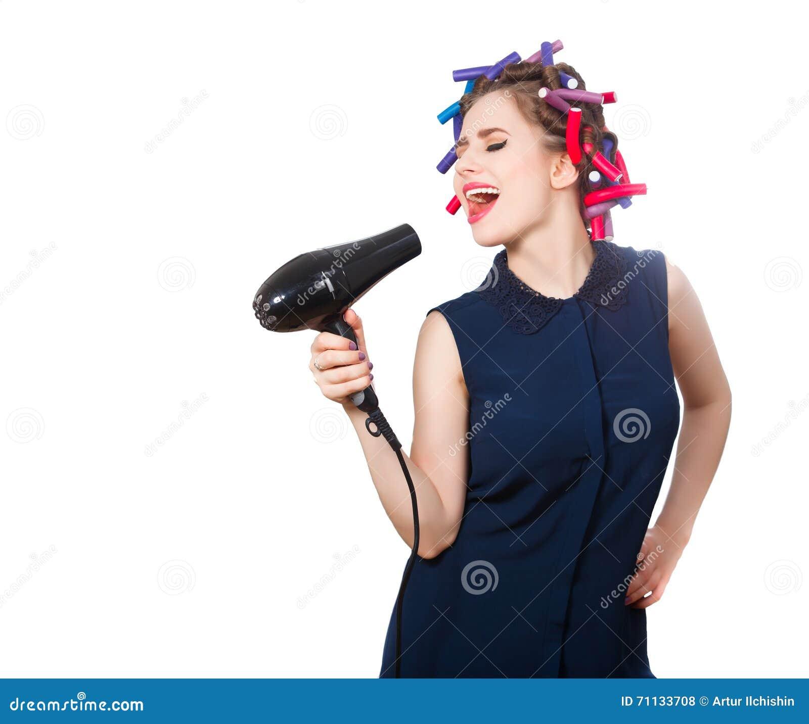 Foto van jonge zingende vrouw in krulspeld met hairdryer