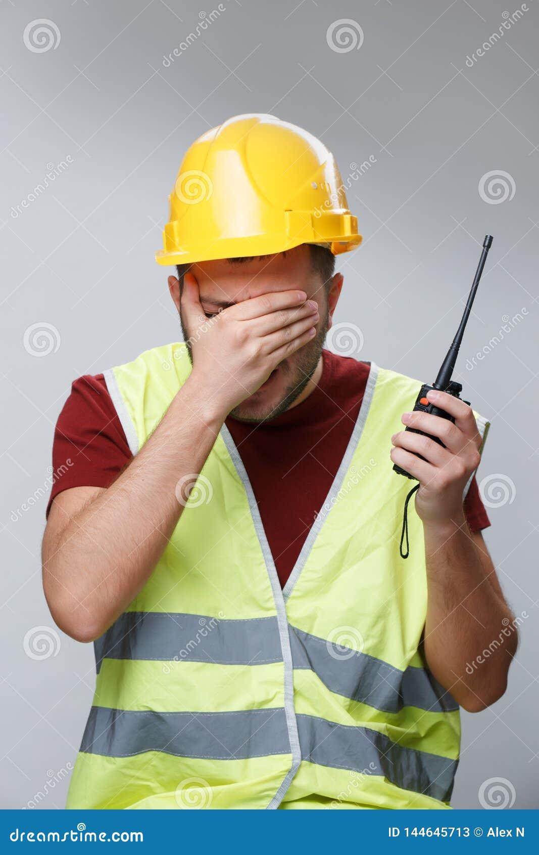 Foto van ongelukkig bouwersmannetje in gele helm met walkie-talkie op lege grijze achtergrond