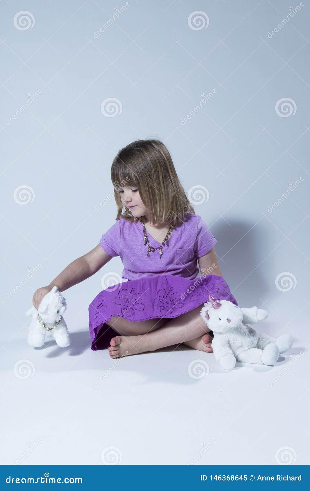 Foto vertical de la niña linda en la falda superior y púrpura de color de malva que se sienta a piernas cruzadas