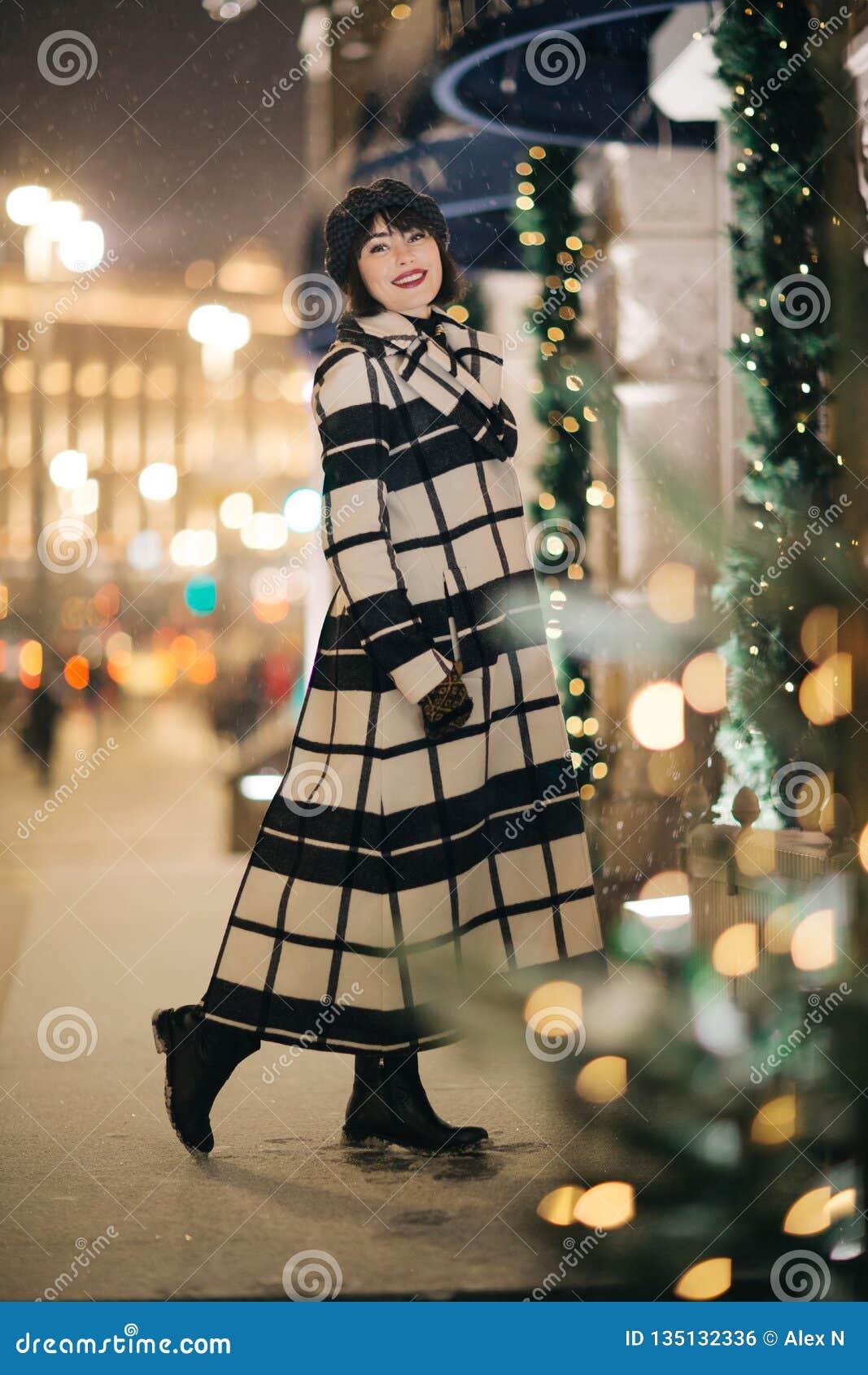 Foto von Brunette in voller Länge in der Straße auf unscharfem Hintergrund
