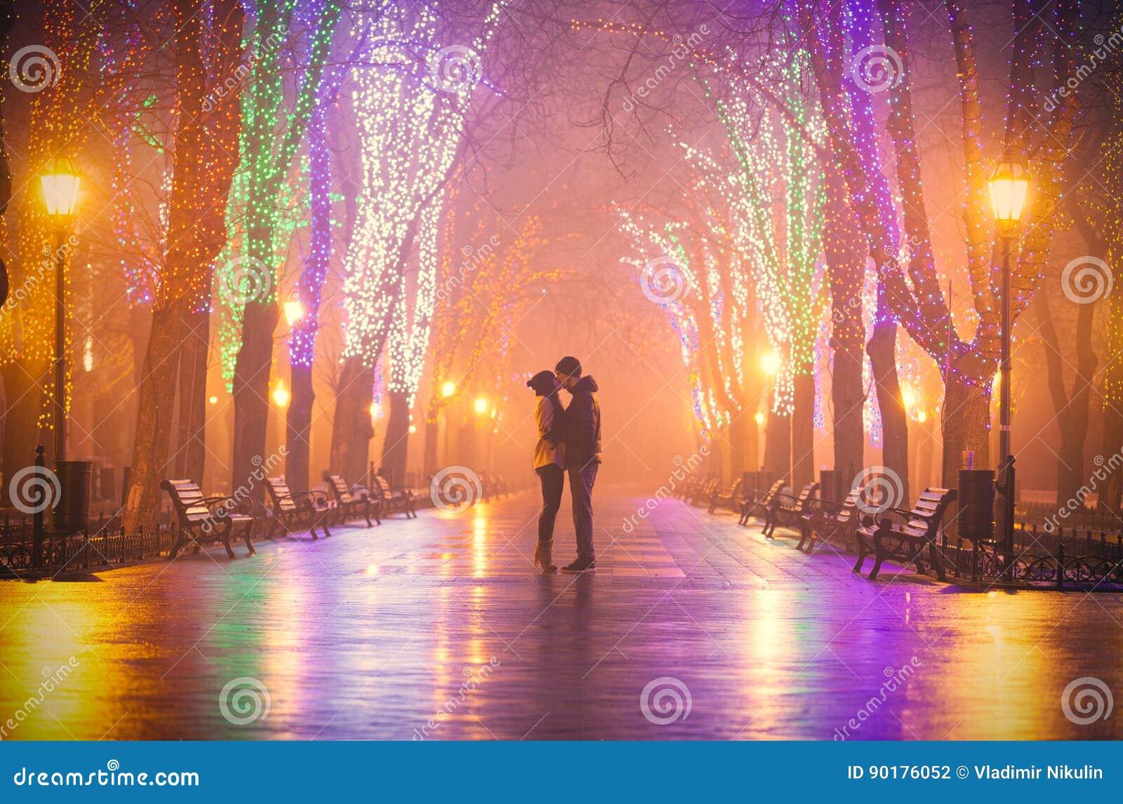Fotoet av gulliga par som kysser på den wondeful natten, parkerar backgrou