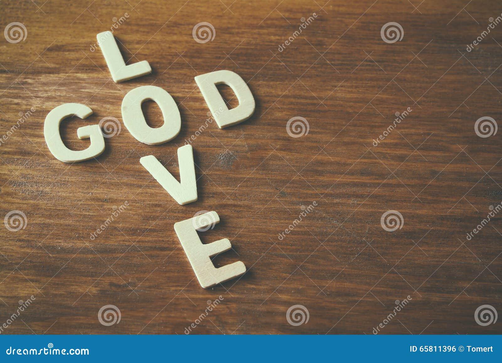 Fotoet för den selektiva fokusen av ordförälskelsen är guden som göras med kvarterträbokstäver på träbakgrund religion för bokbeg
