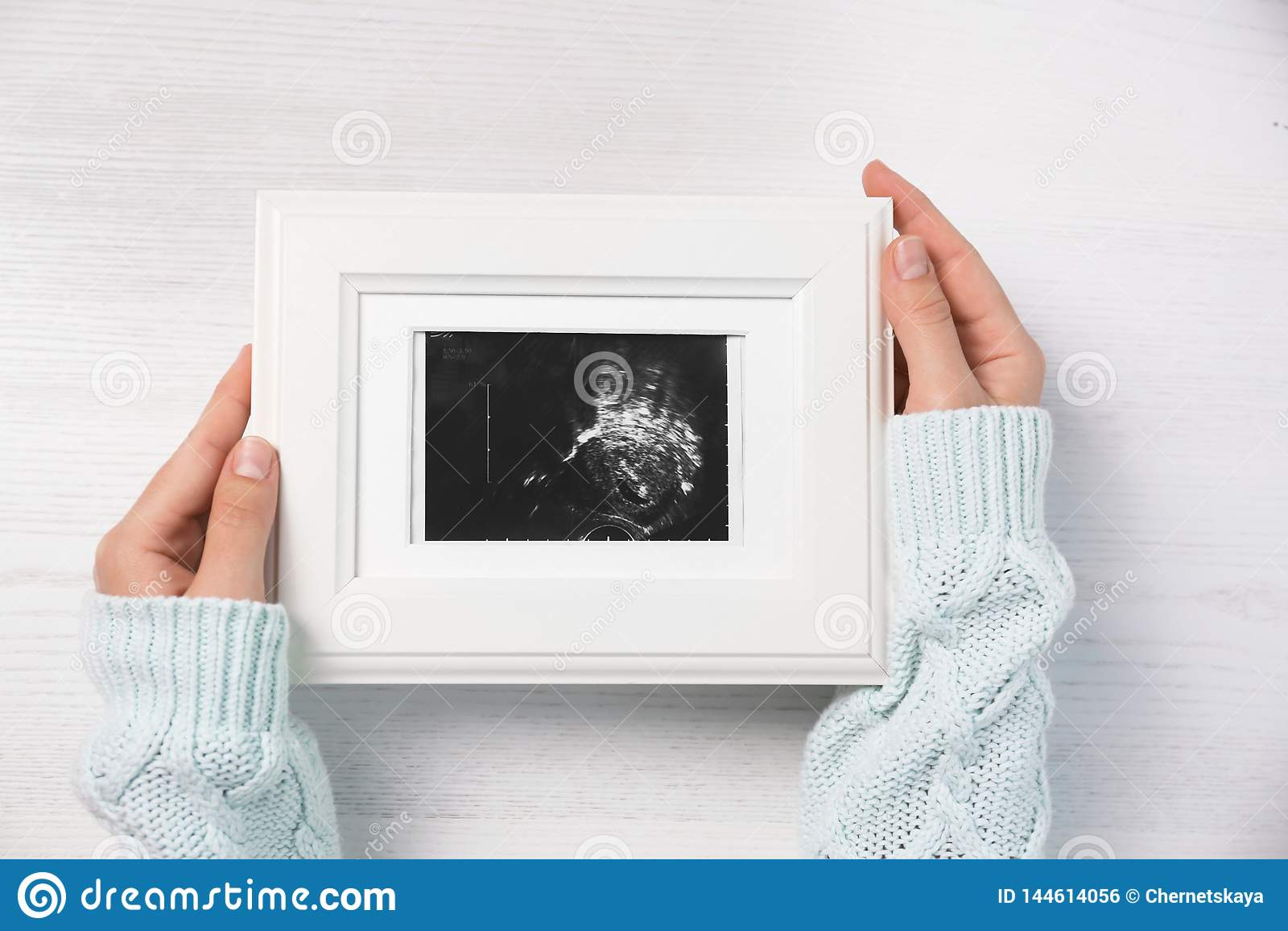 Fotoet för kvinnainnehavultraljudet av behandla som ett barn över trätabell, v