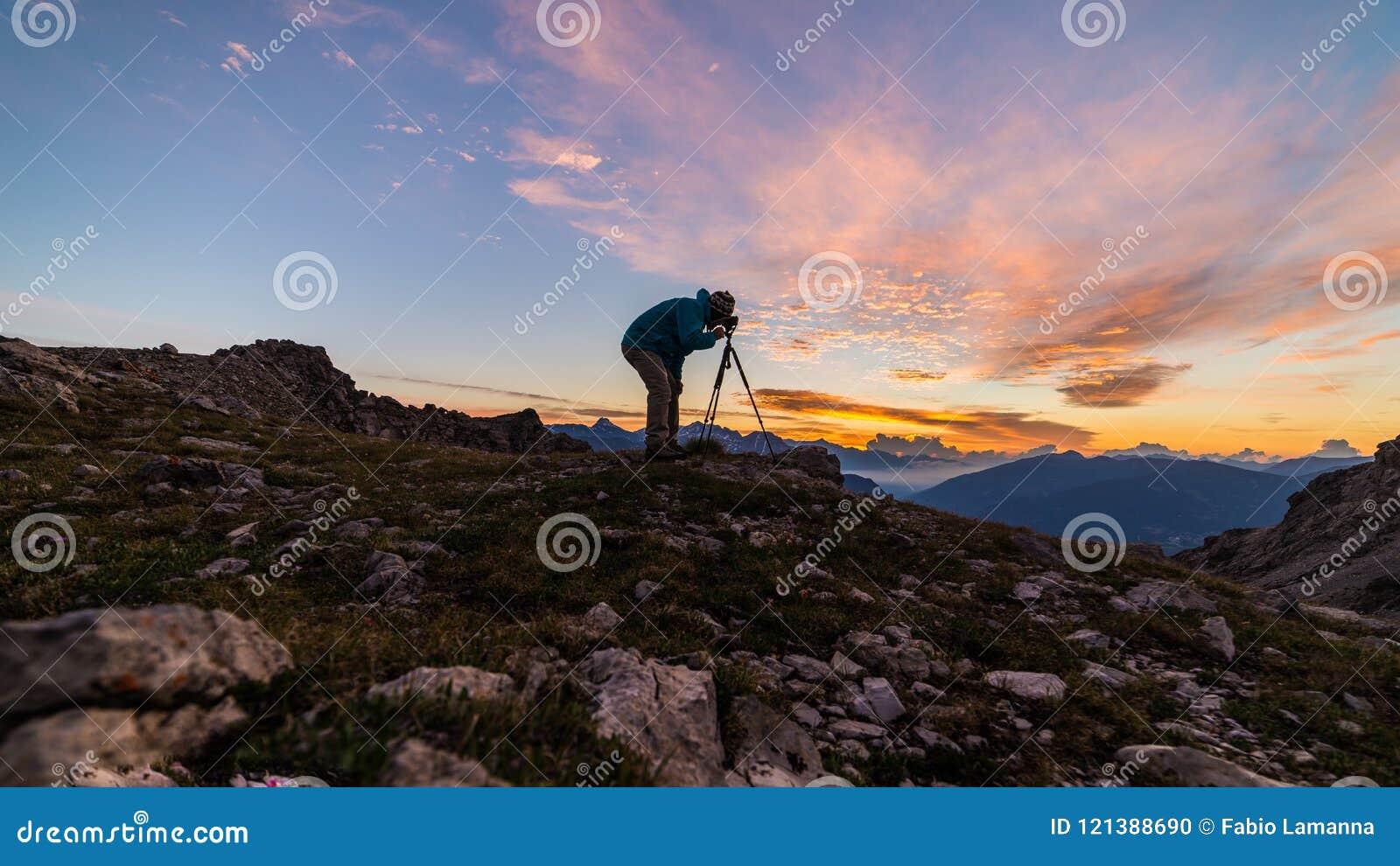 Fotograaf op bergbovenkant met camera op driepoot bij scenislandschap van de zonsopgang licht kleurrijk hemel, het veroveren conc