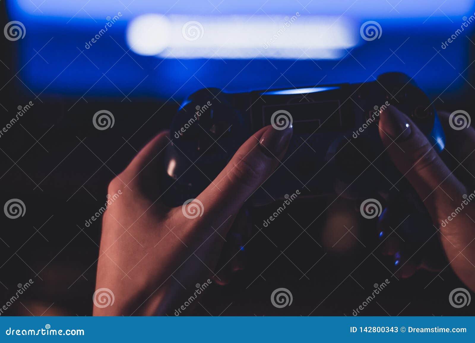 Fotografía atmosférica del geypad en la mano de una muchacha
