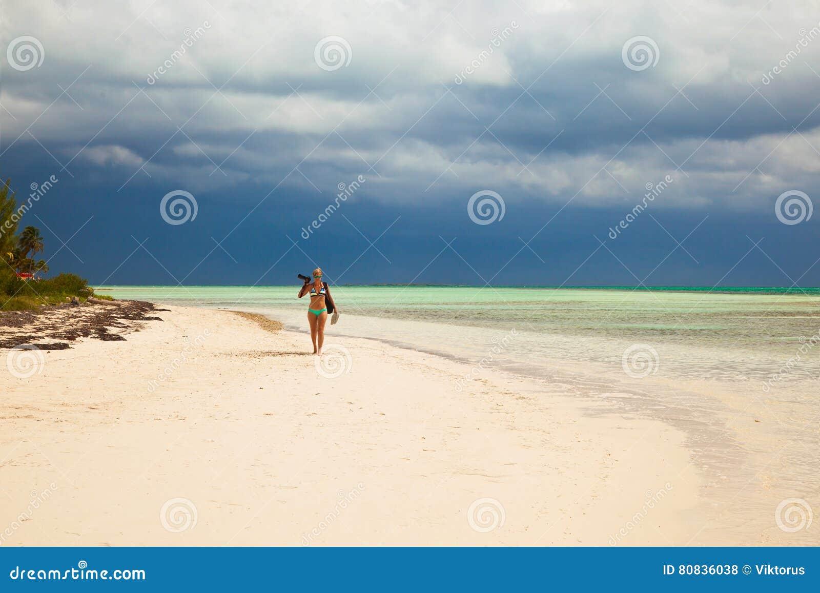 Fotograf junger Dame im Bikini geht auf das karibische tropica
