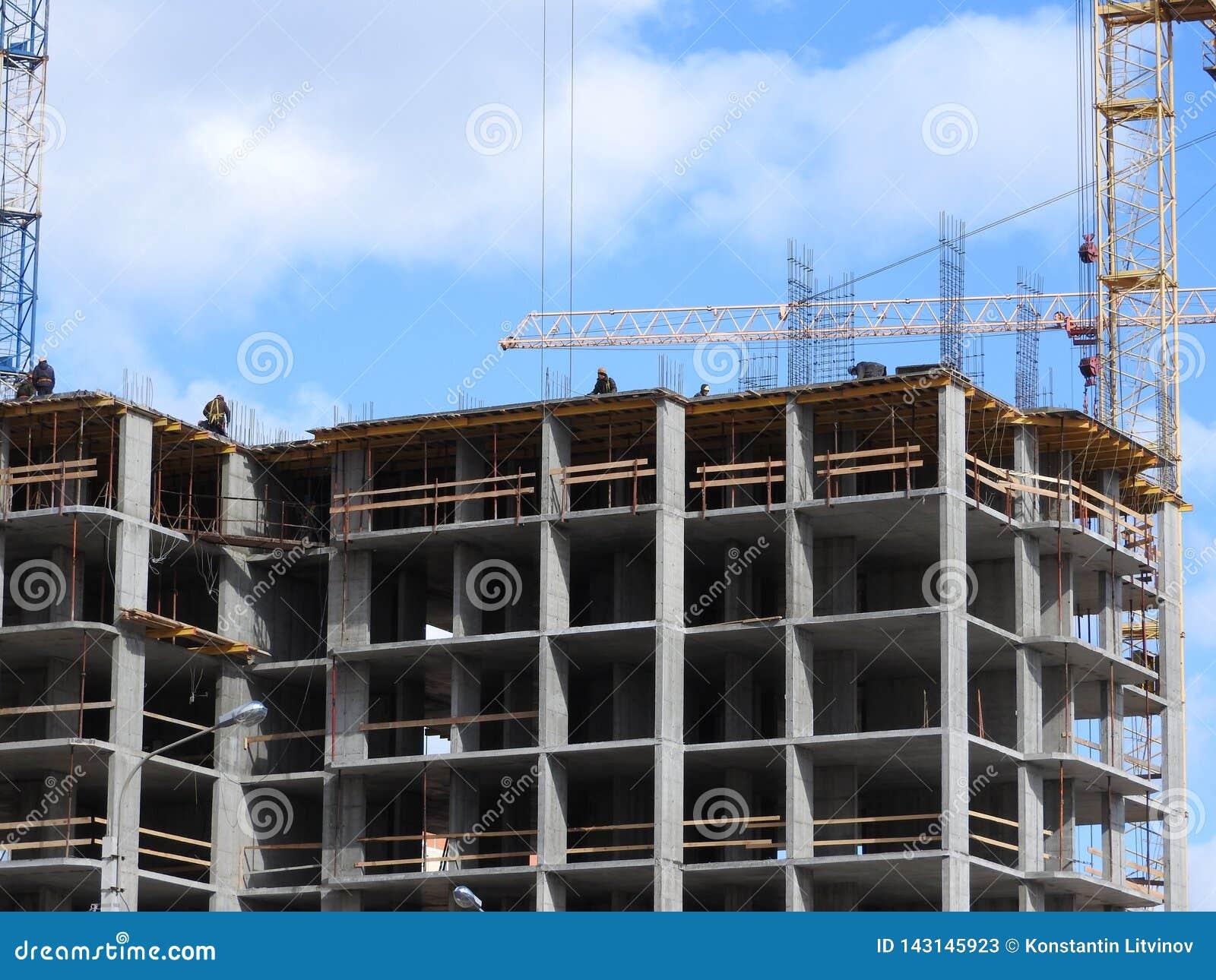 Fotografia aérea de um engenheiro civil não reconhecido sem uma cara, olhando o trabalho de construtores do telhado no canteiro d