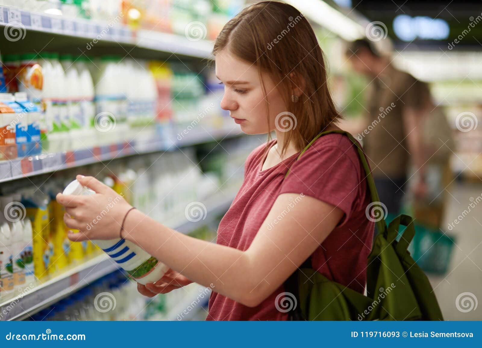 Fotografia atrakcyjny młody żeński konsumenta model z kiwającą fryzurą, ubierająca w przypadkowej t koszula, stojaki w dużym skle