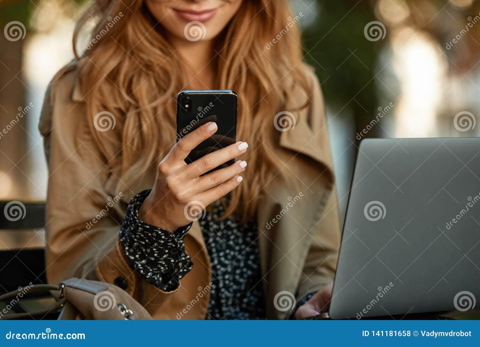 Fotografia bizneswoman używa telefon komórkowego i laptop w nasłonecznionej alei podczas gdy siedzący na ławce