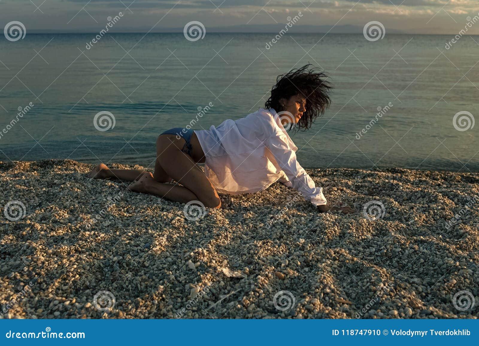 Fotografia da forma pelo mar A mulher está em todos os fours, rasteja na praia na noite A menina  sexy , veste a camisa branca e