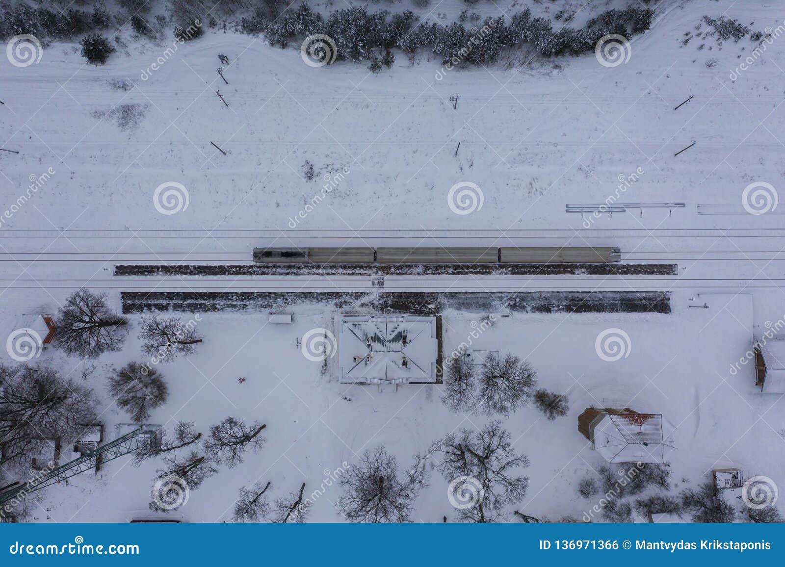 Fotografia do zangão da floresta do inverno, da locomotiva na estação e da estrada de ferro