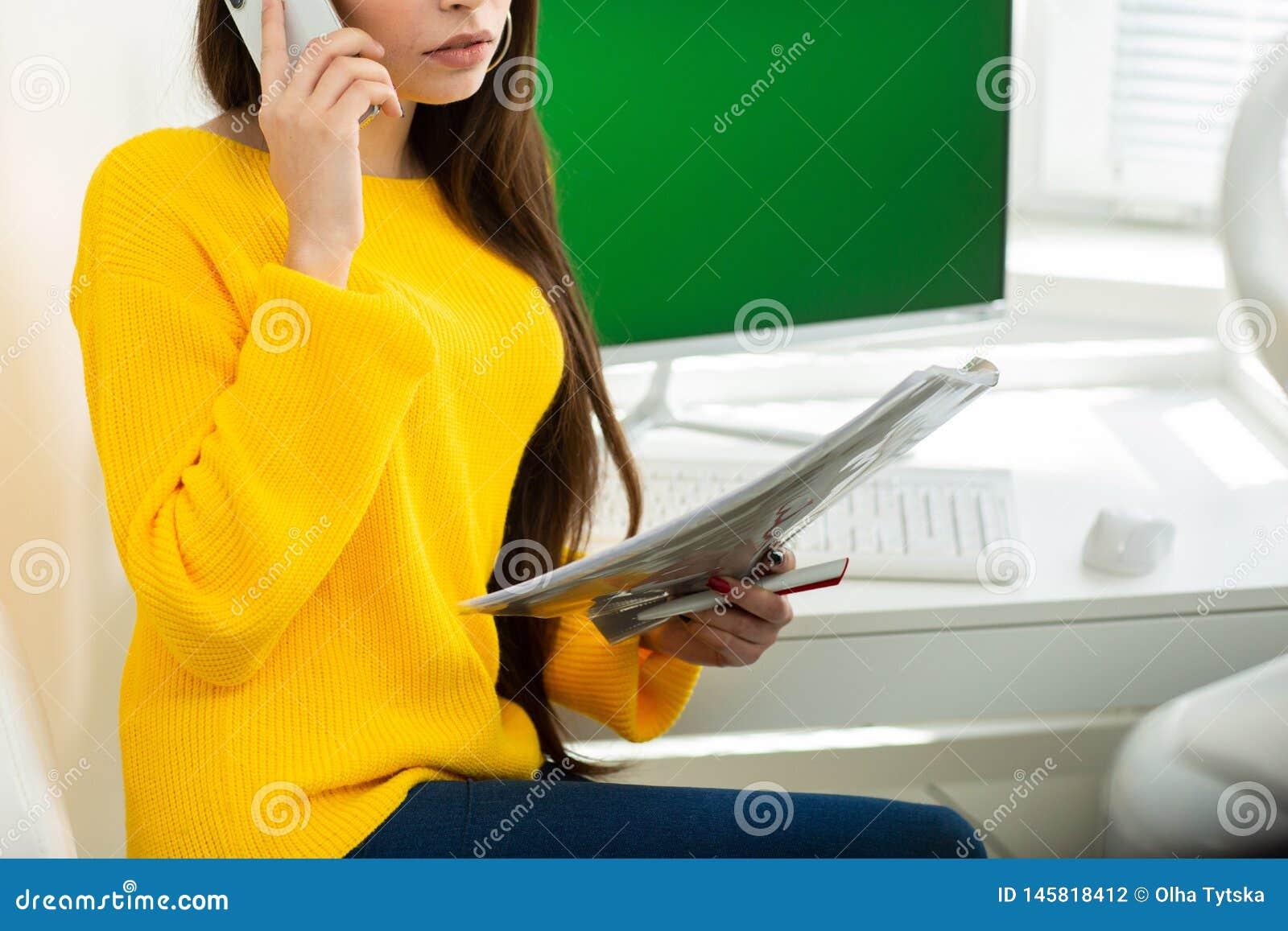 Fotografia kobieta, opowiadający na telefonu i czytania dokumentach w biurze Zielony ekran w tle