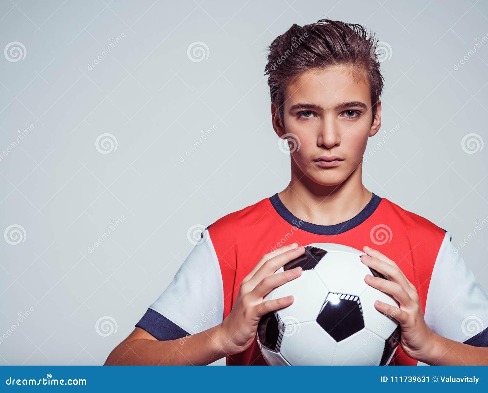 Fotografia nastoletnia chłopiec w sportswear mienia piłki nożnej piłce
