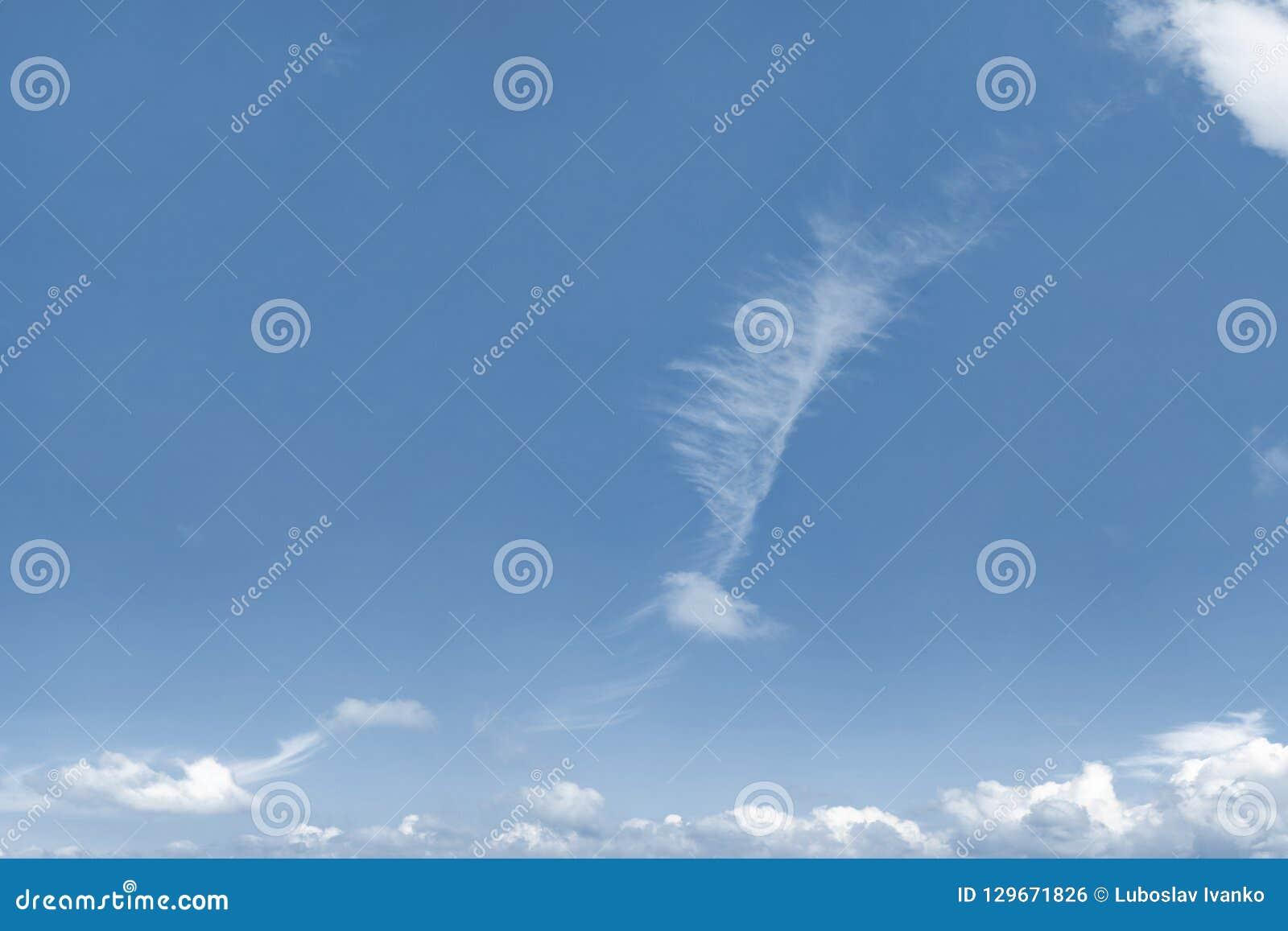 Fotografia niebieskie niebo z dziwnie kształtną chmurą