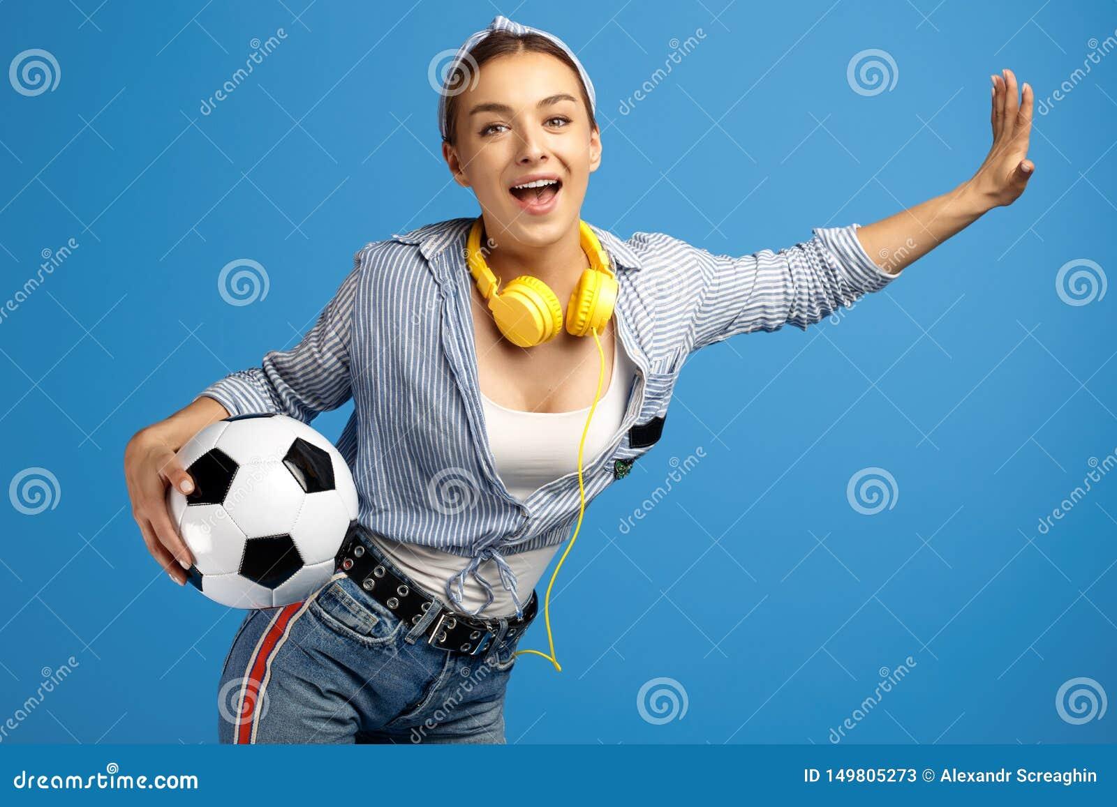 Fotografia urocza młoda kobieta z, piłki nożnej piłka, hełmofony, i tanczymy nad błękitnym tłem