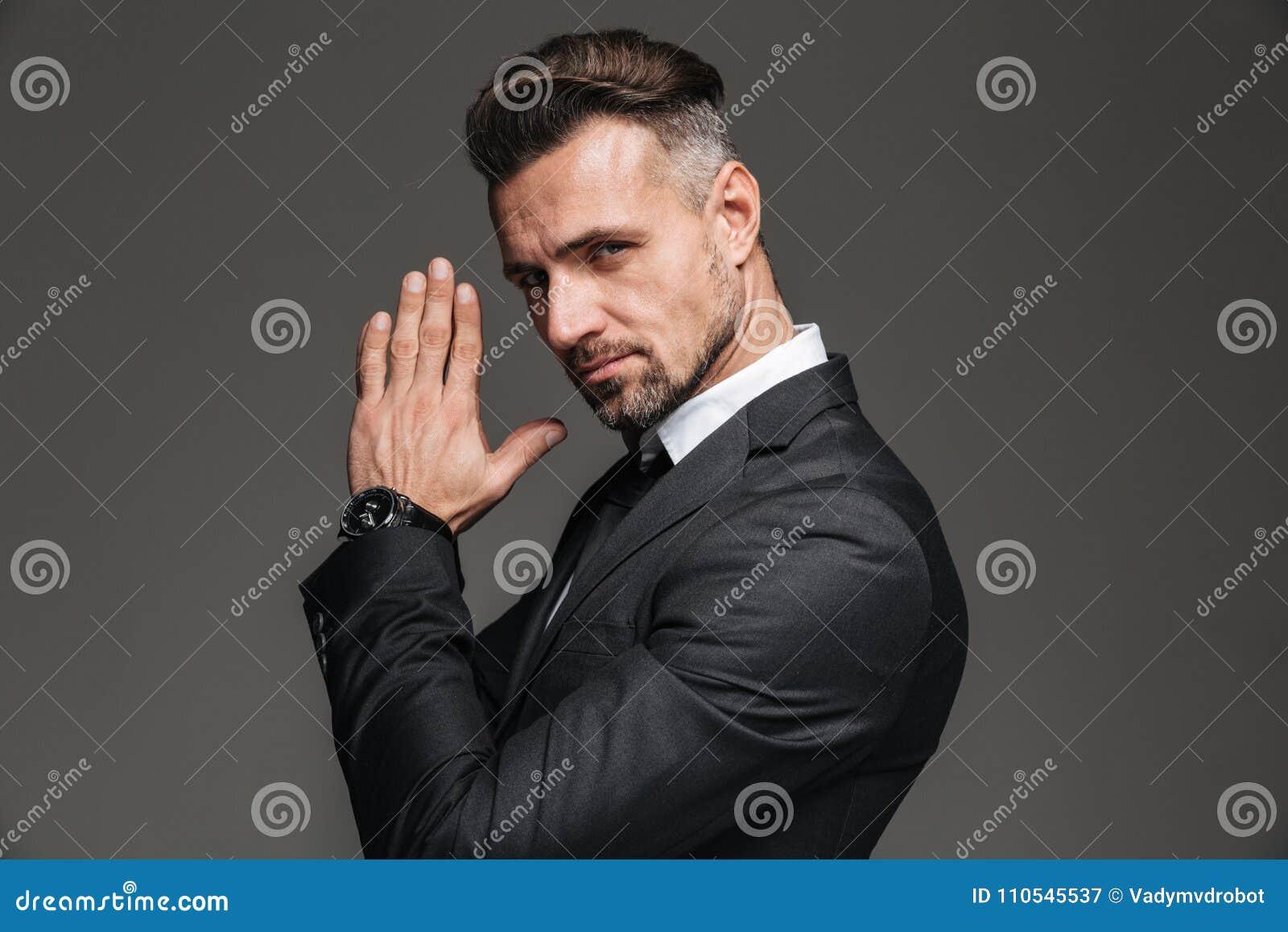 Fotografia w profilu elegancki dorosły mężczyzna 30s w czarny kostiumu patrzeć