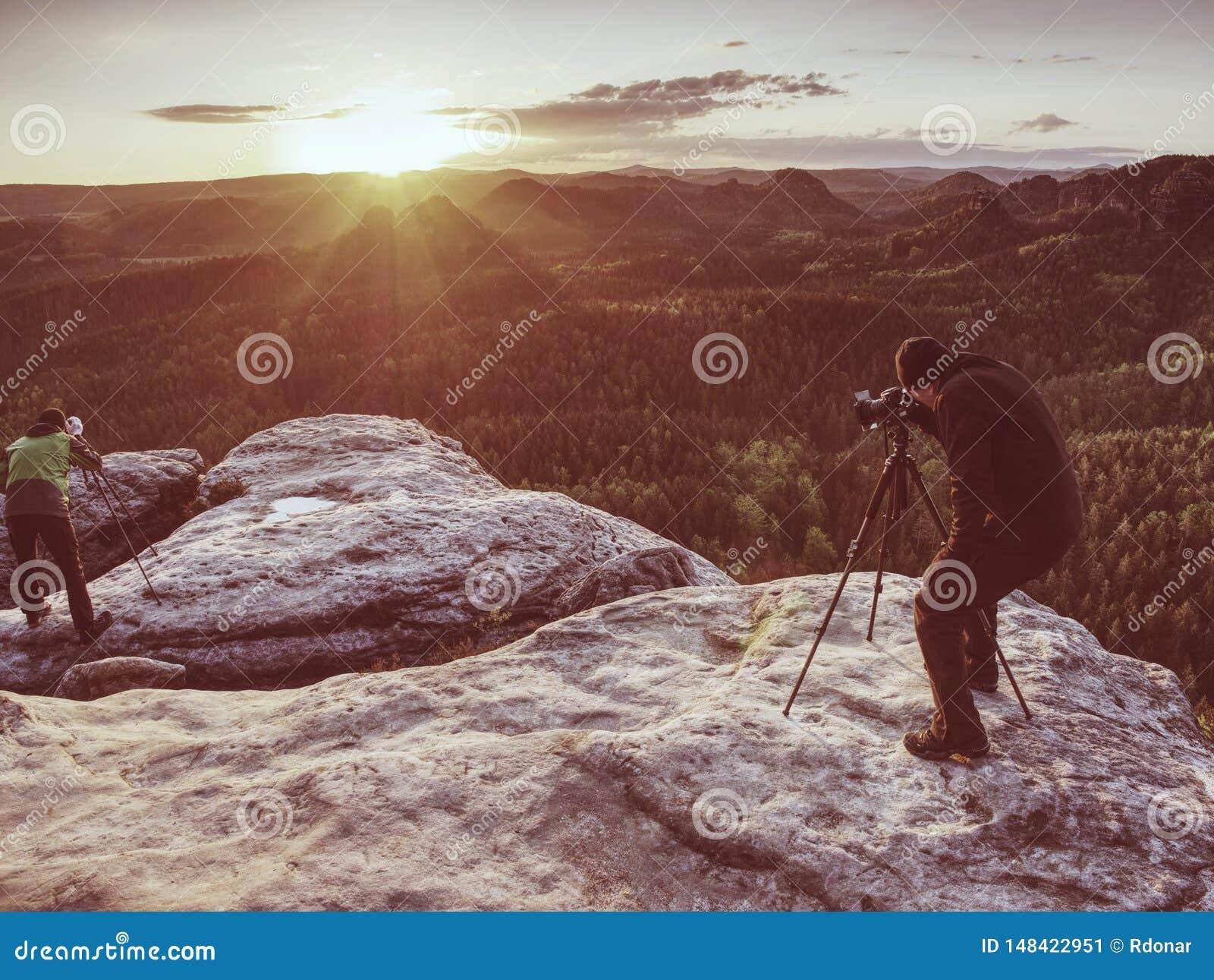 Fotografkontrollsk?rm av kameran p? tripoden Manstag p? klippan