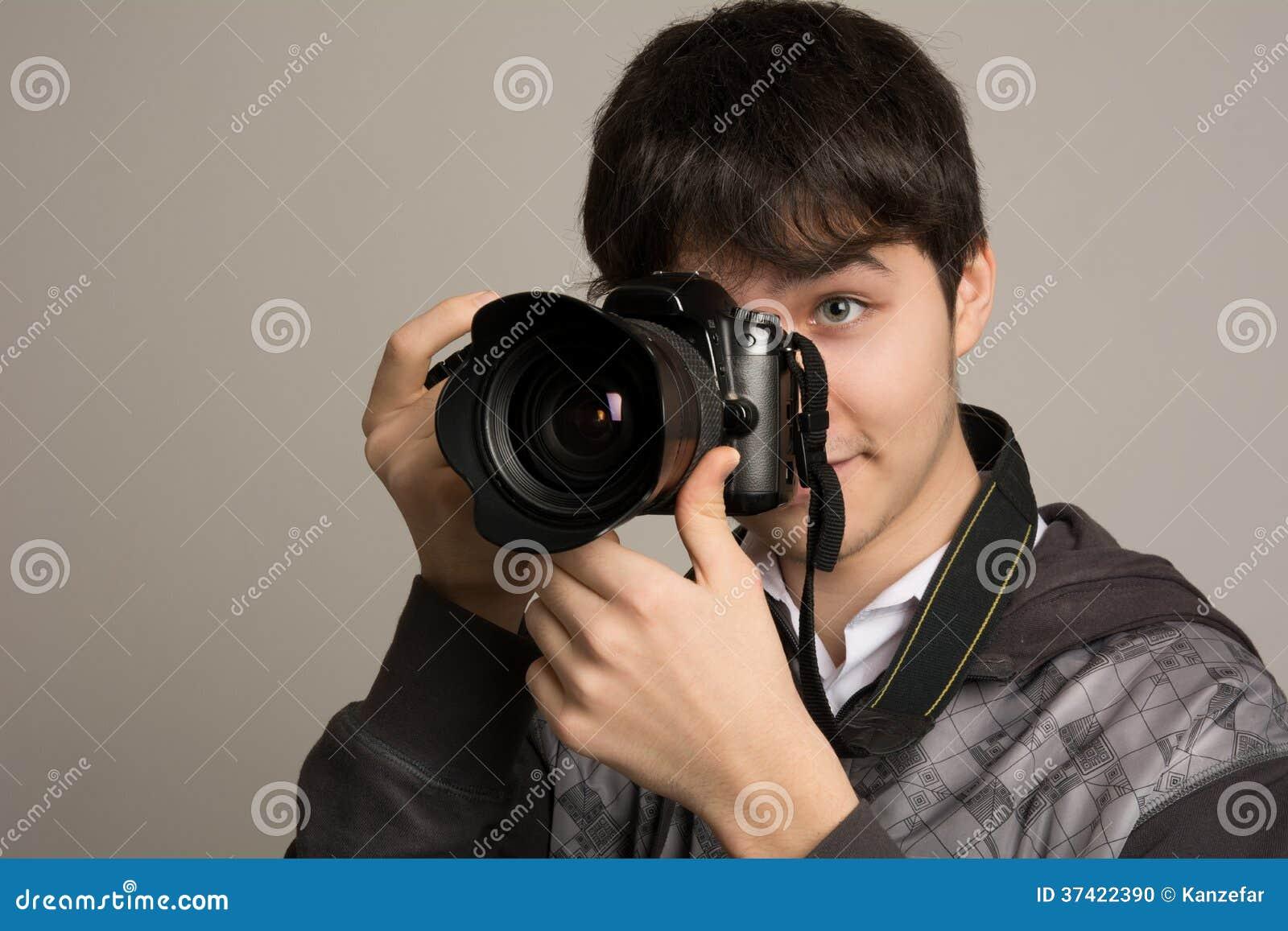 Fotografo maschio che prende le foto con la macchina fotografica digitale di DSLR