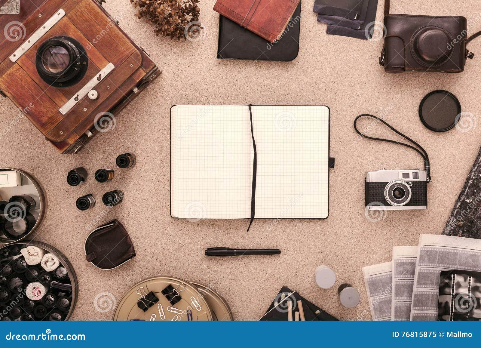 Fotografs skrivbord med den öppna urklippsboken, tappningkameror och rullar av filmen Lekmanna- lägenhet