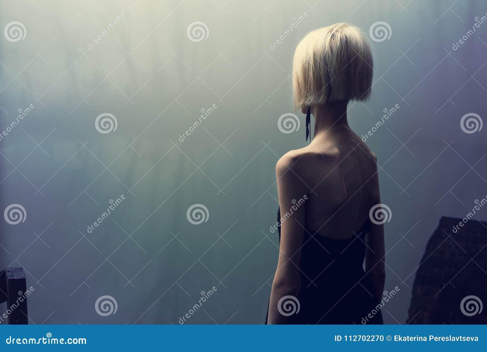 Fotoperiod vid sjön på en dimmig dag i skogen, mager flicka i svart klänning