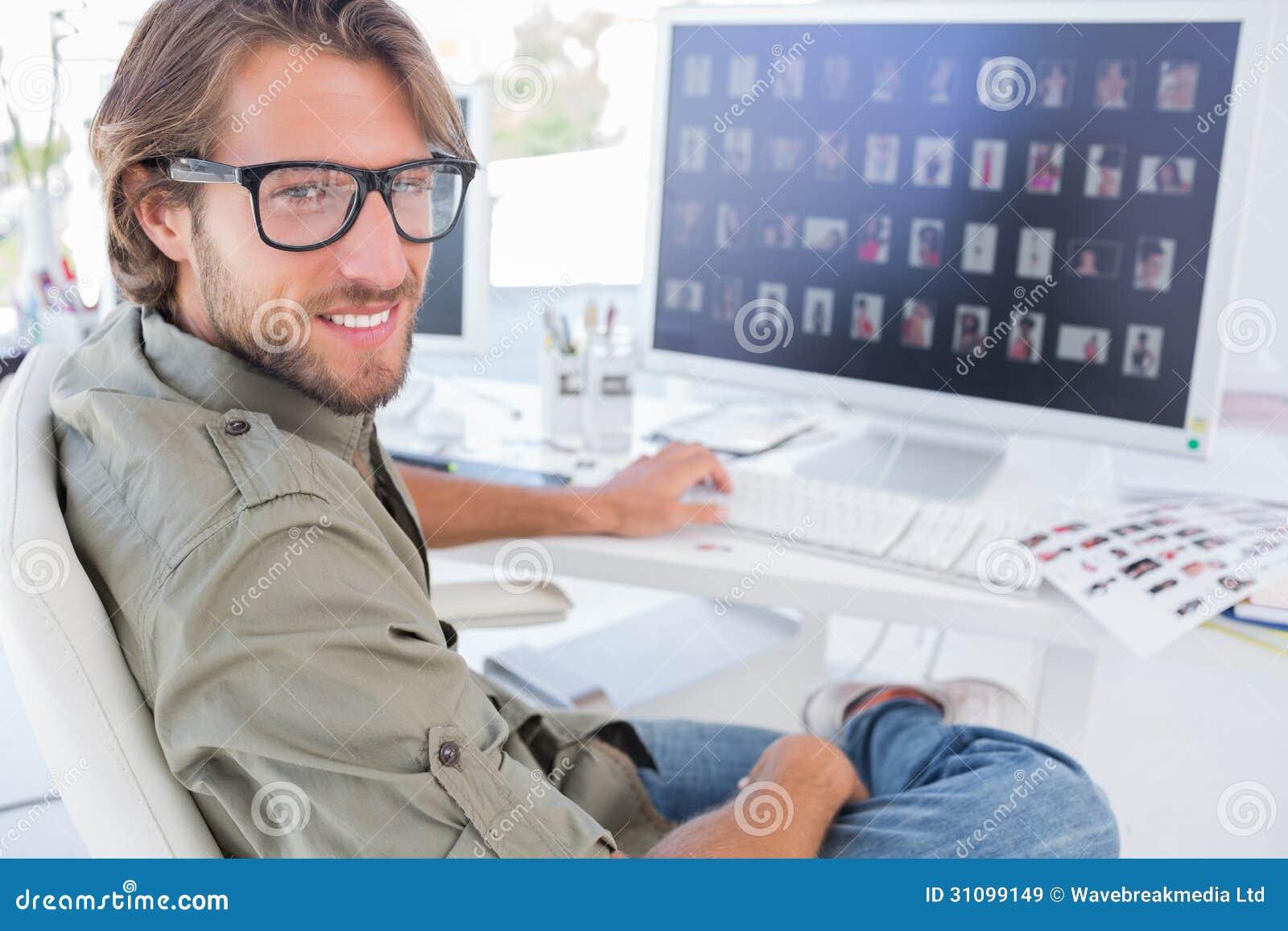 Fotoredacteur die en bij zijn bureau draaien glimlachen