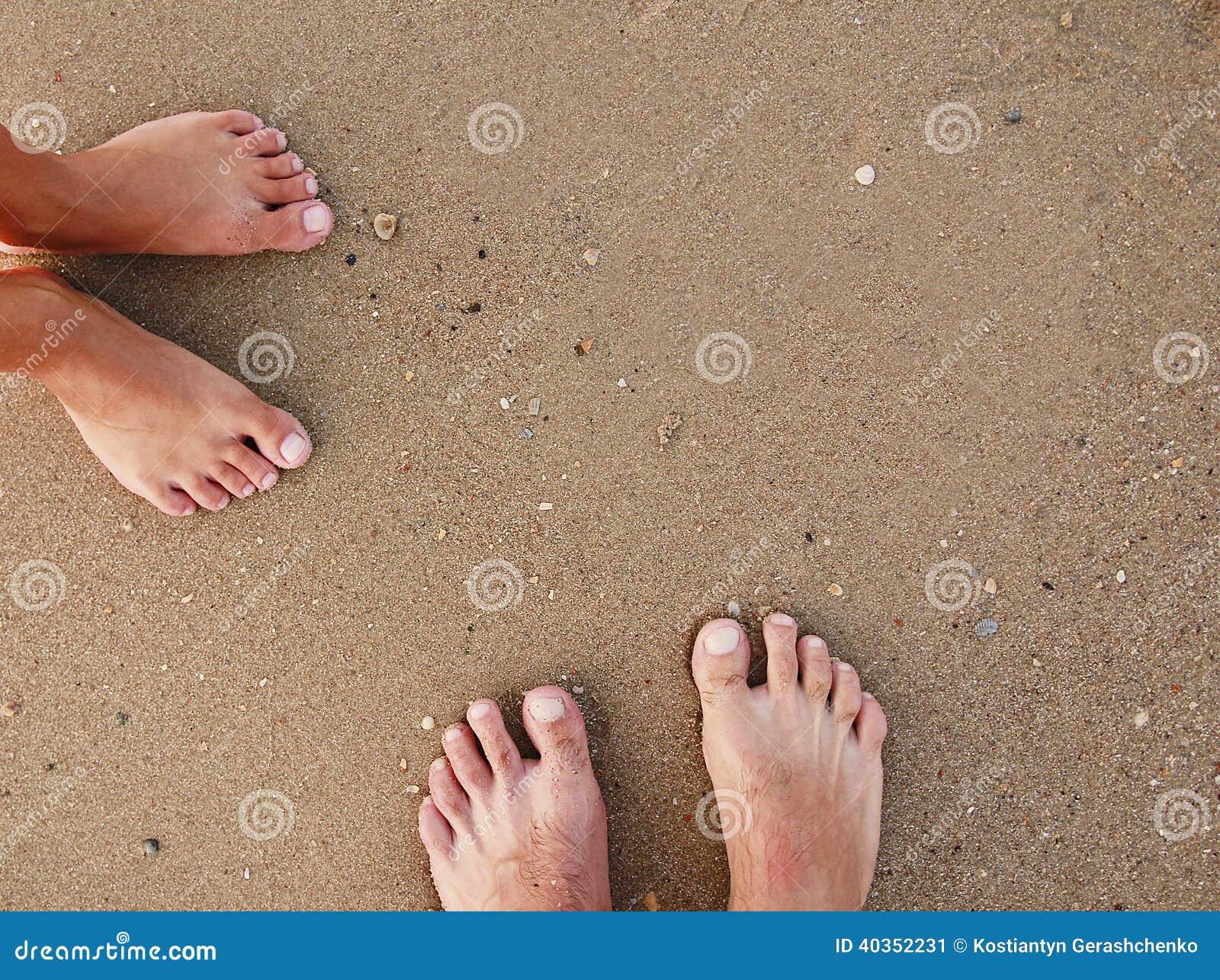 Fotspår av ett älska par i sanden på kusten