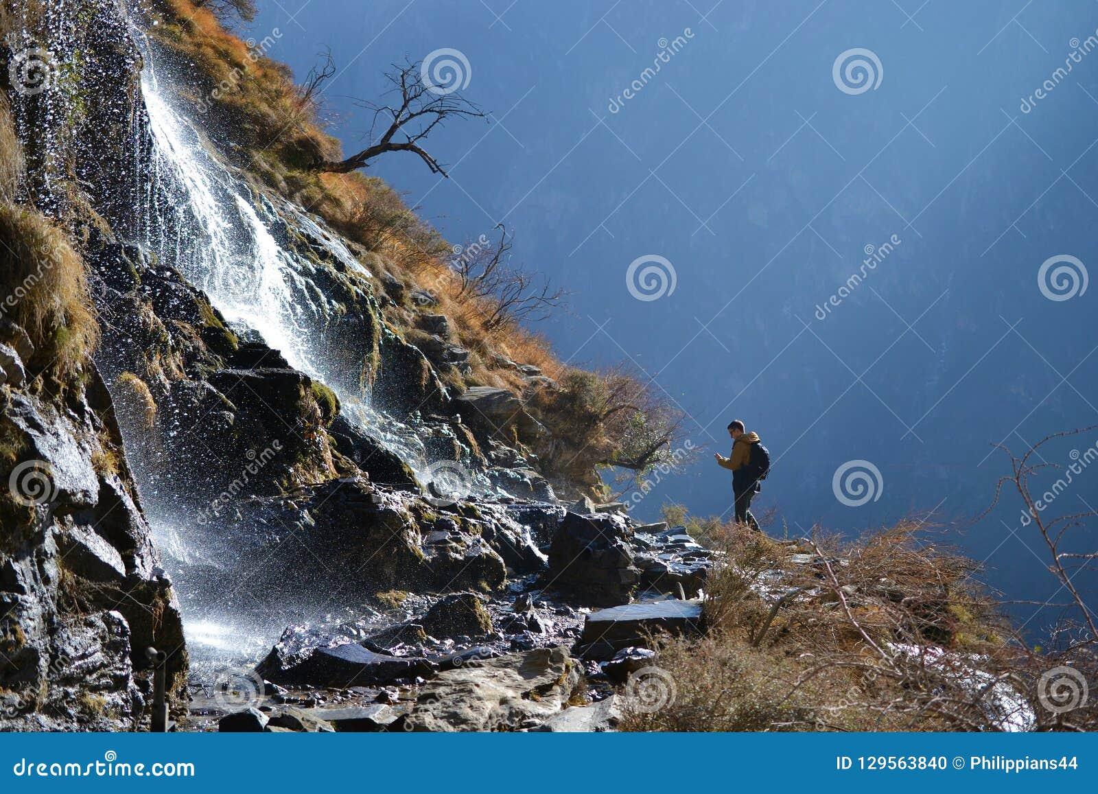 Fotvandra i Tiger Leaping Gorge Berg och flod Mellan Xianggelila och den Lijiang staden Yunnan landskap, Tibet, Kina
