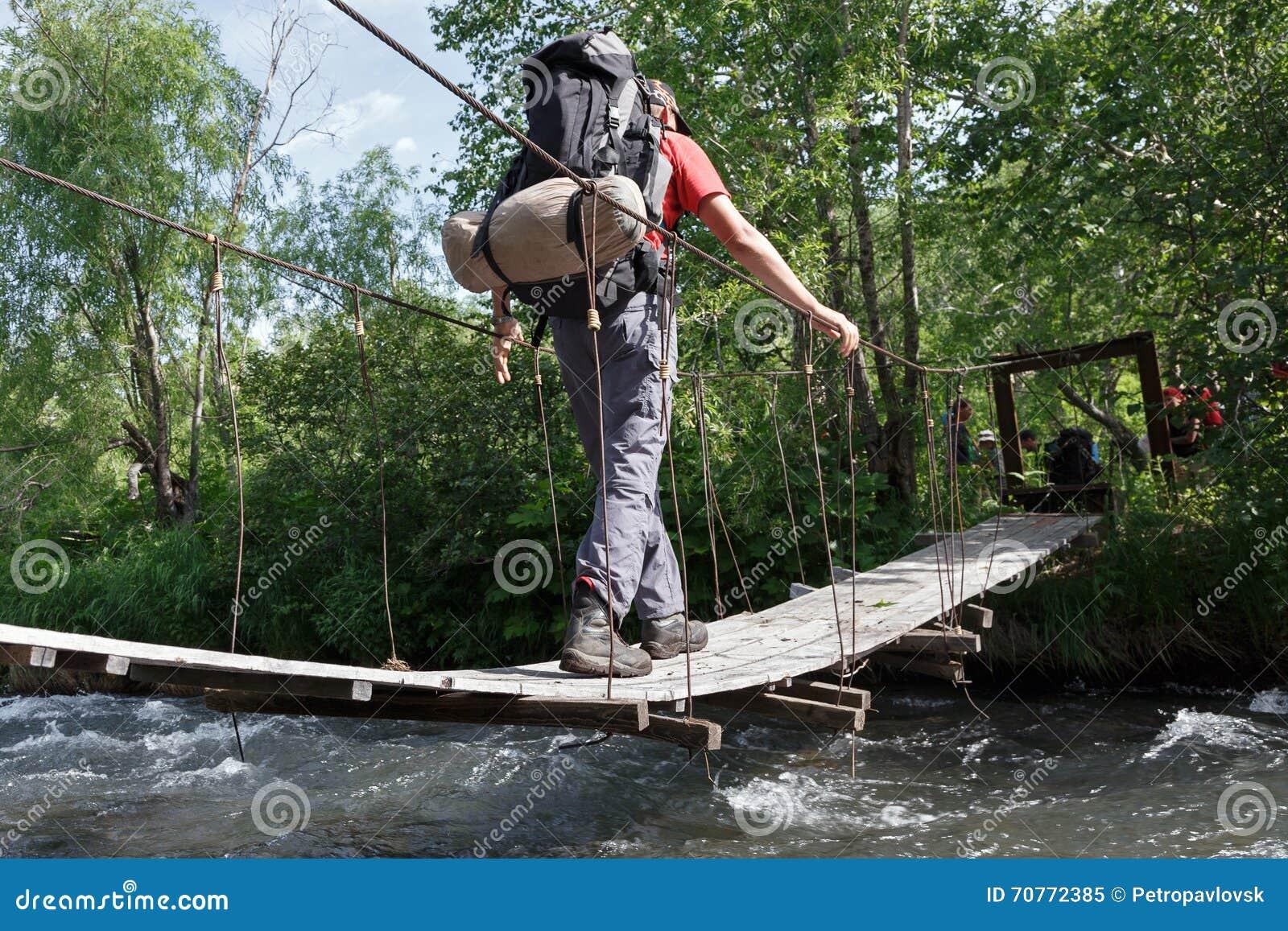 Fotvandra på Kamchatka: turist- korsning bergflod på upphängningbron