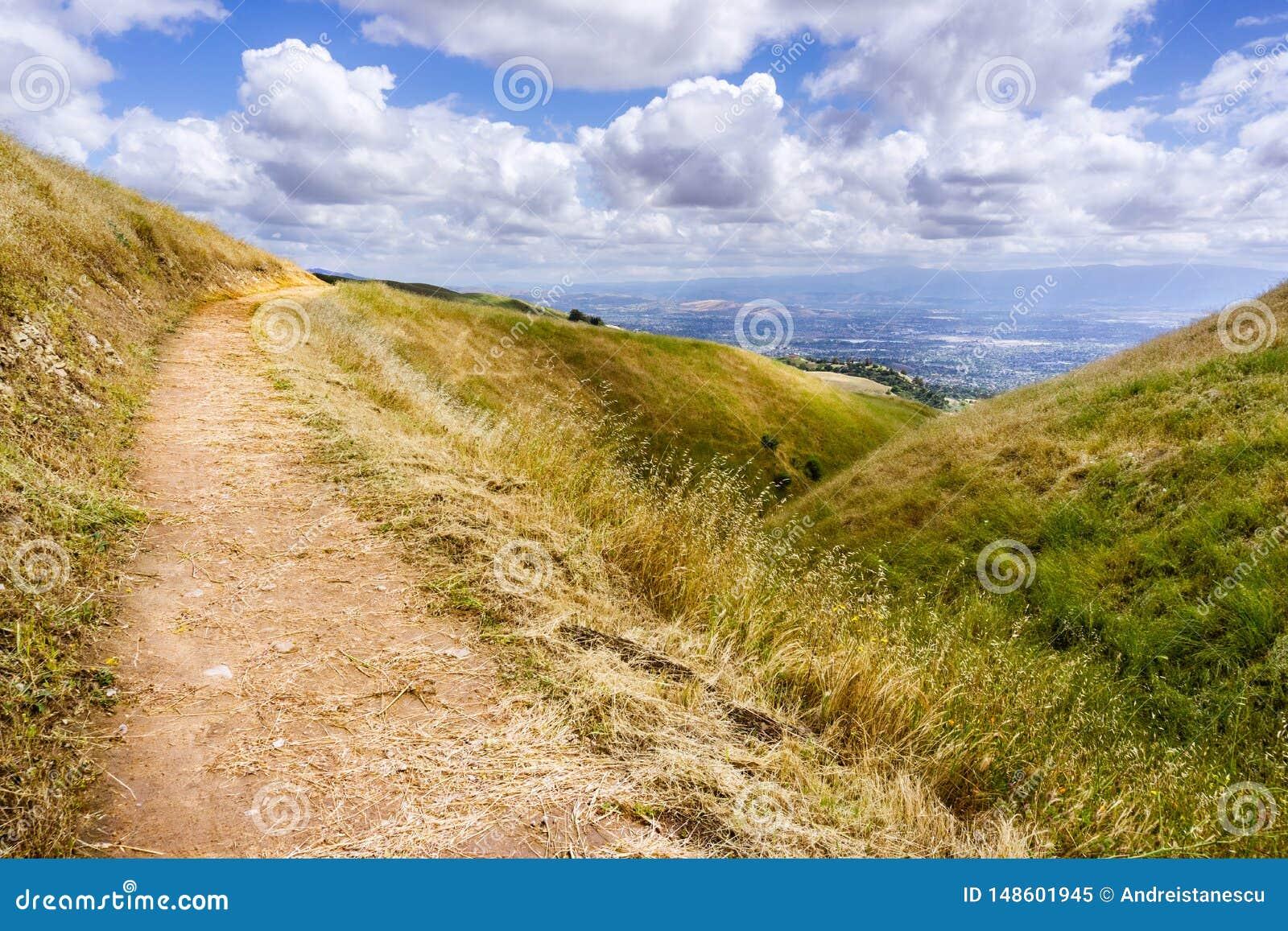 Fotvandra slinga till och med kullarna av södra San Francisco Bay område, San Jose som är synligt i bakgrunden, Kalifornien