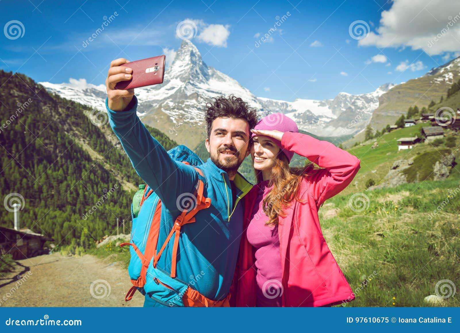 Fotvandrare för ett par som fotvandrar med ryggsäckar, promenerar ett härligt bergområde