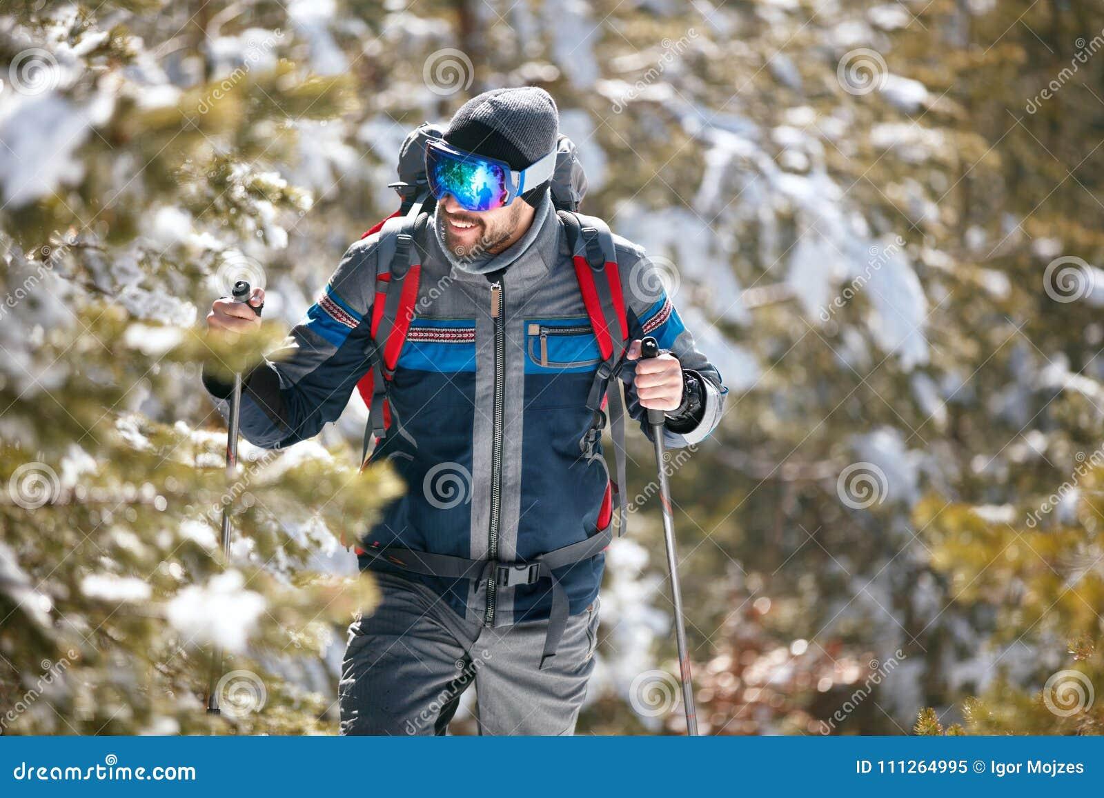 Fotvandrare med ryggsäcken som trekking i berg Kallt väder, snö på