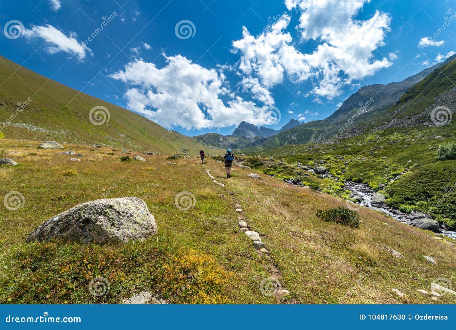 Fotvandrare med stora ryggsäckar som fotvandrar på berget Kackarlar