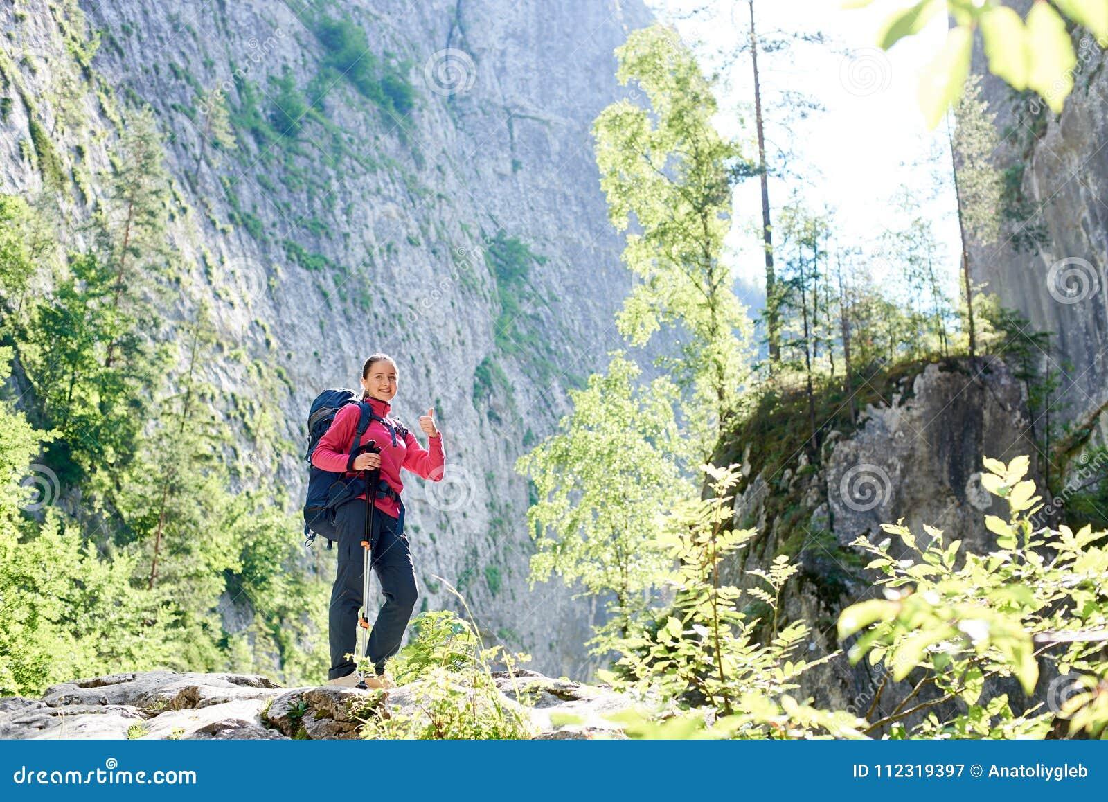 Fotvandrareflicka som står nära den jättelika klippaväggen