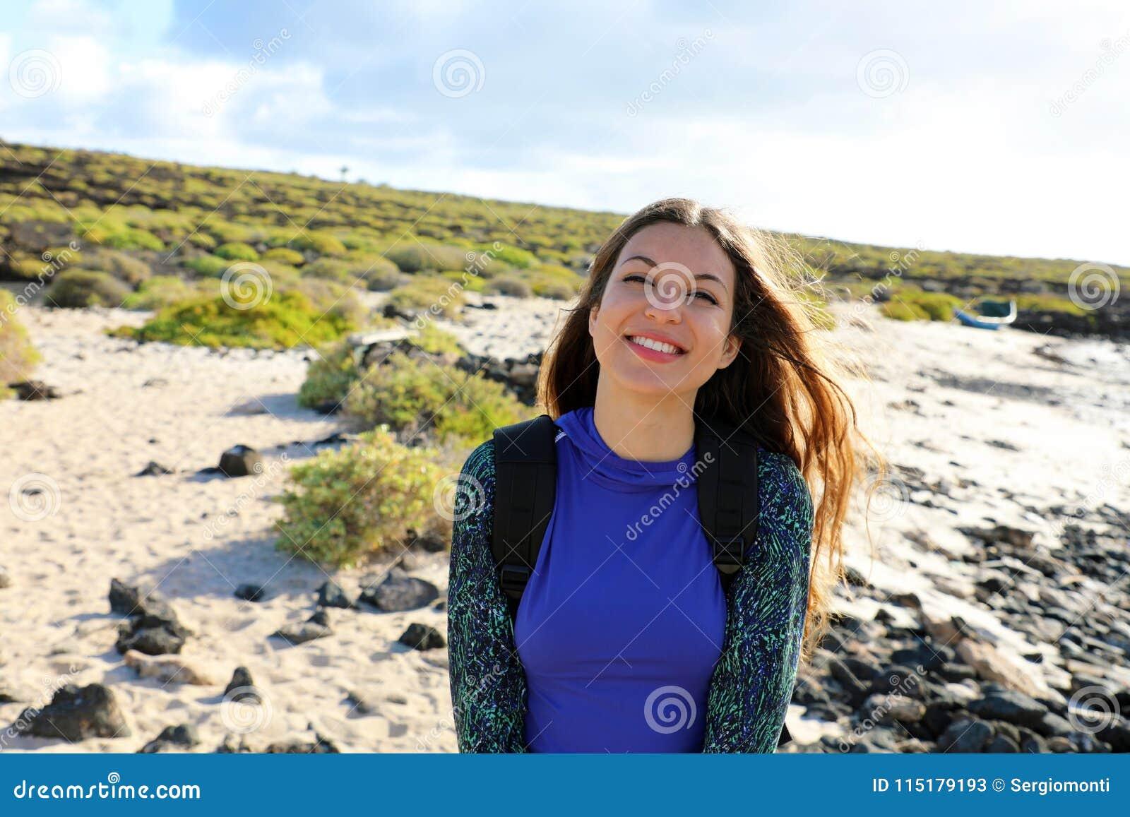 Fotvandrareflicka som utomhus ler på kameran Lycklig ung handelsresandekvinna som undersöker Lanzarote kullar och stränder i en s