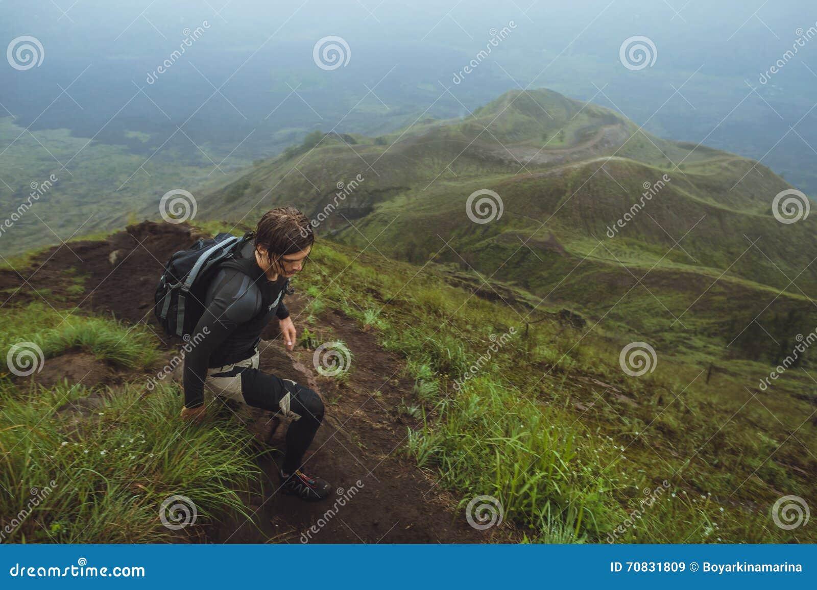 Fotvandrareman som klättrar en brant vägg i berg